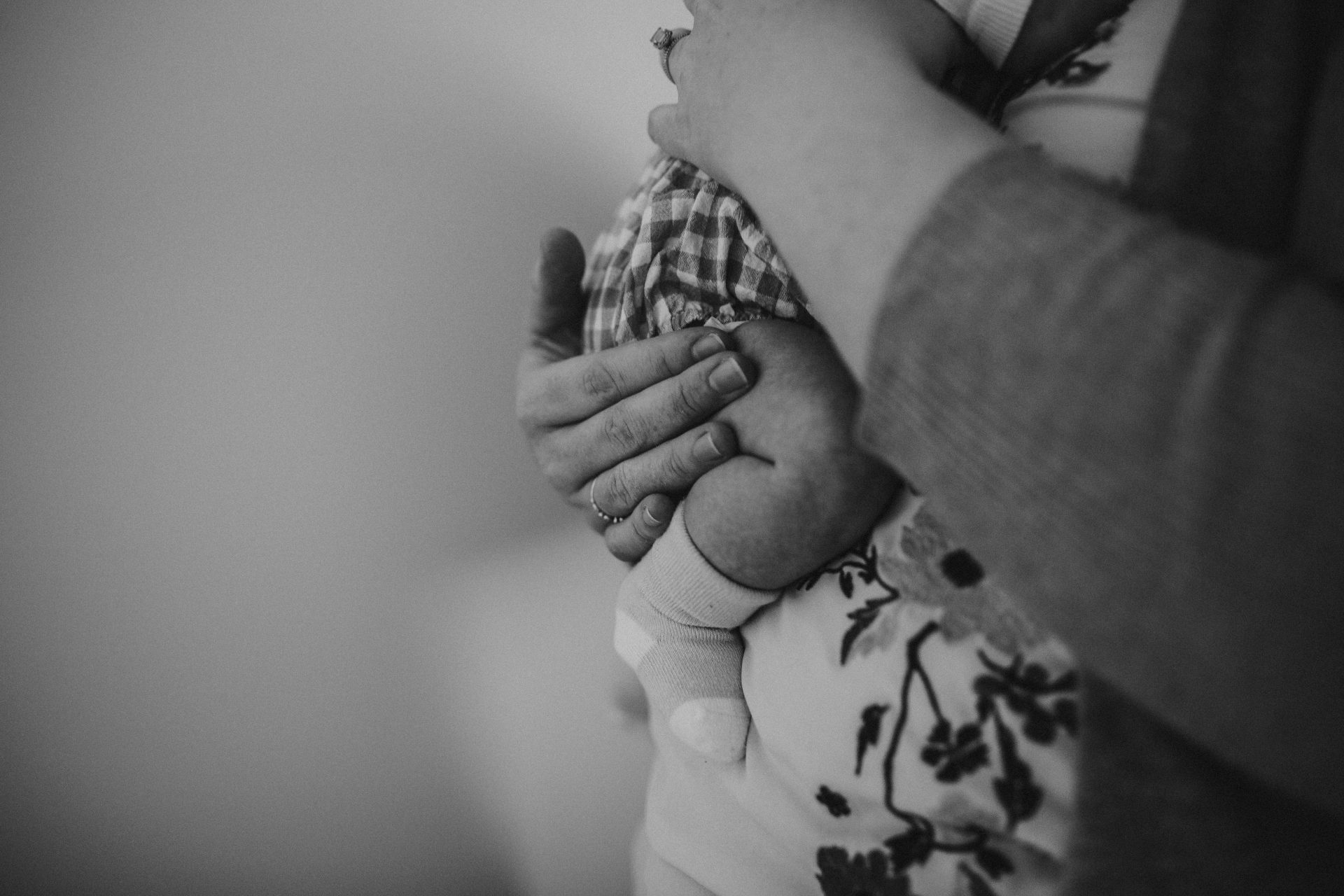Black and white close up of mother cradling newborn in her hand