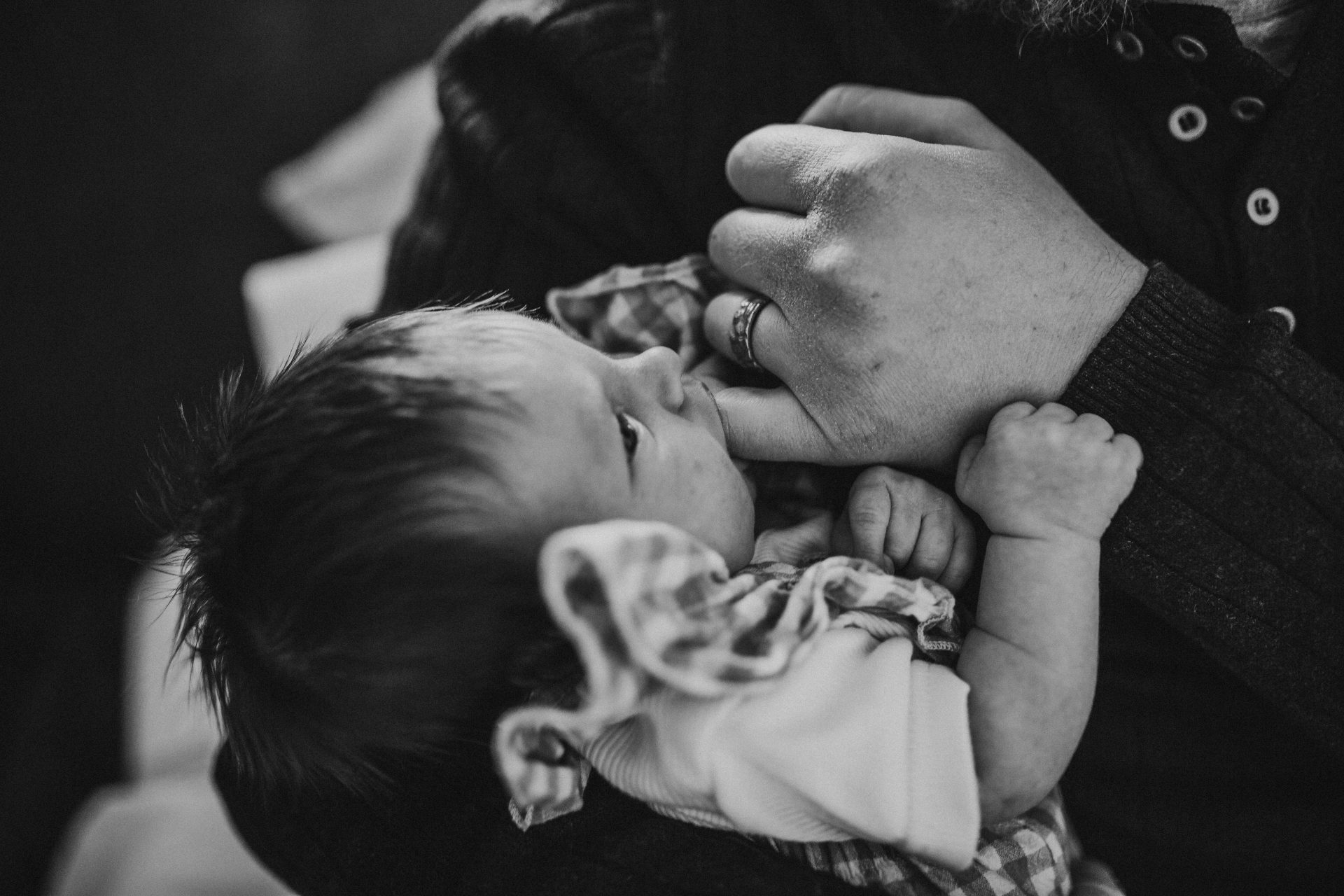 Black and white image of father using pinky finger as pacifier for newborn baby girl