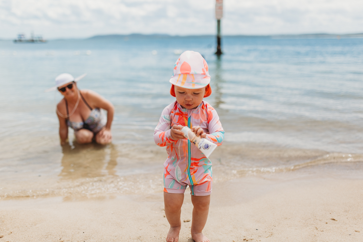 Toddler with tube of sunscreen at the beach