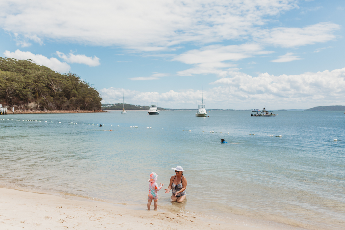 Toddler with grandmother playing at the beach in Shoal Bay