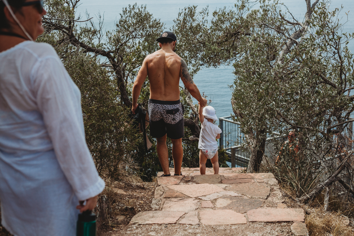 Father holding toddler's hand as they walk down stairs at Mt Tomaree