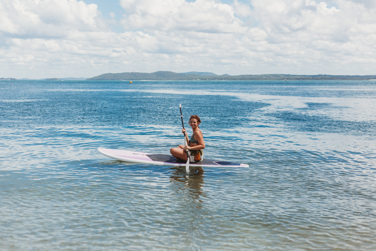 Girl smiling while sitting on stand up paddle board