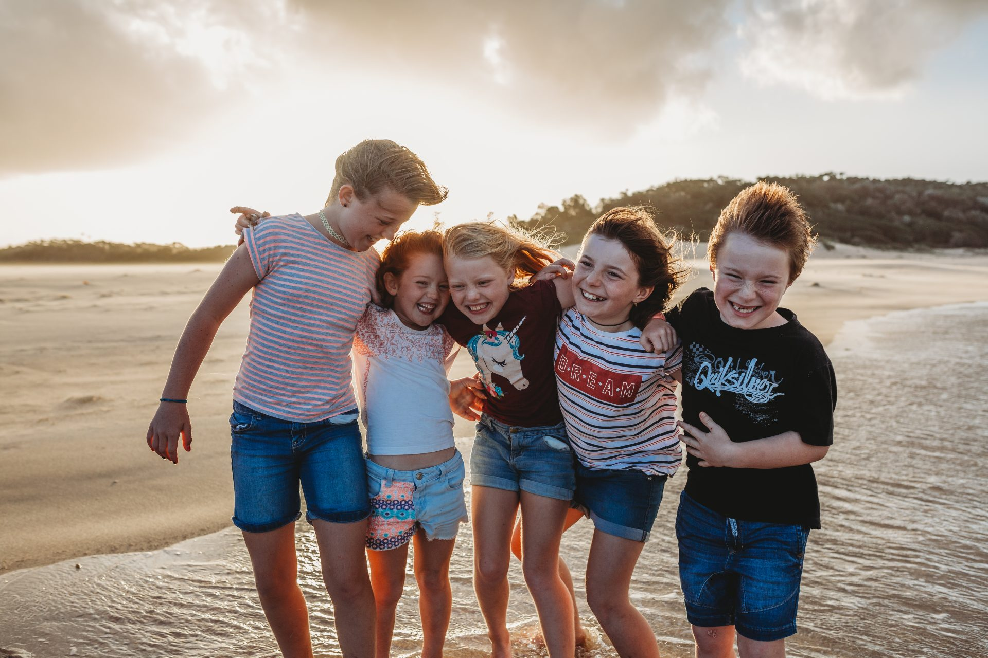 Four girls and a boy standing in a line, hugging and laughing at Lake Tabourie Beach