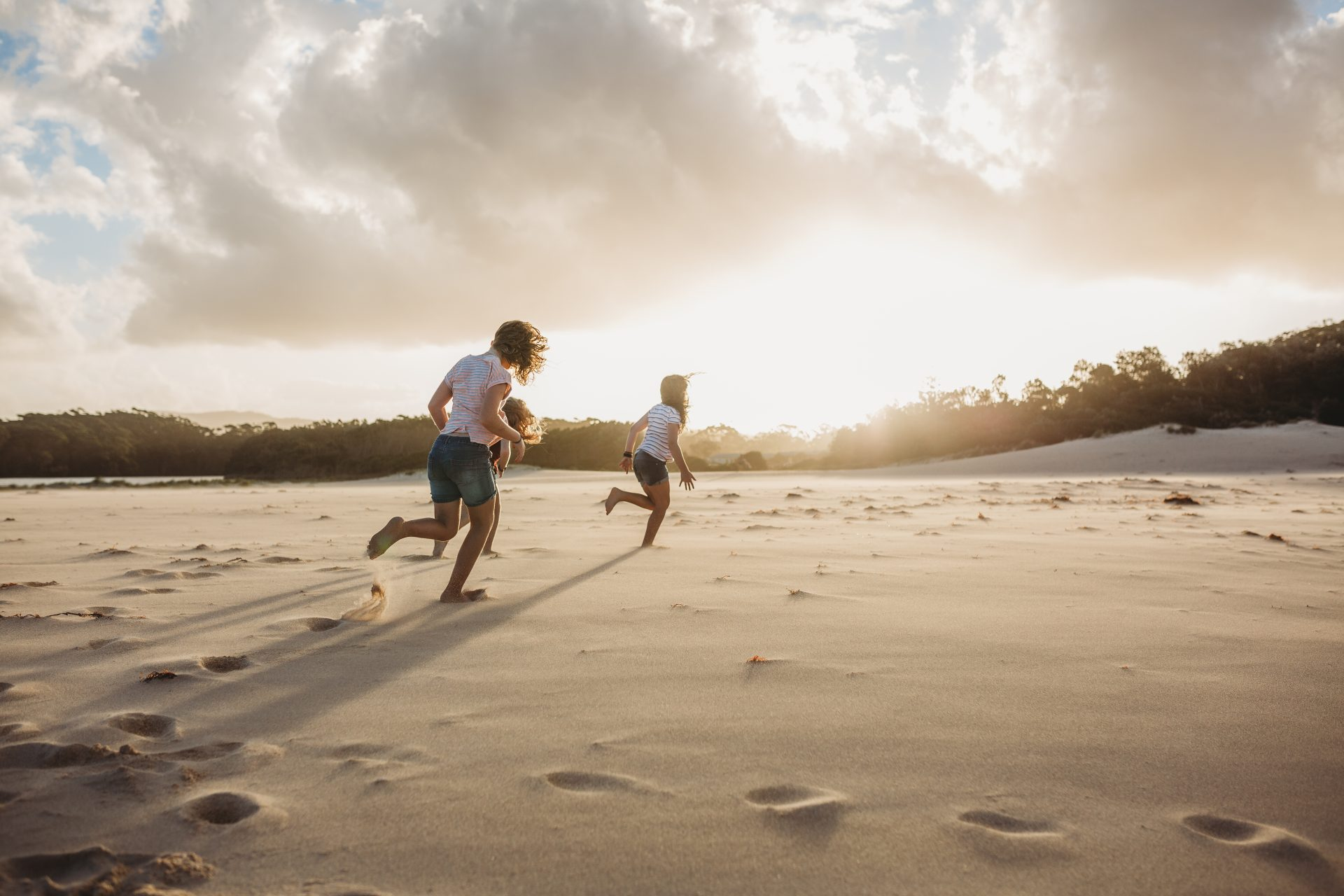 Young kids running along the beach at sunset