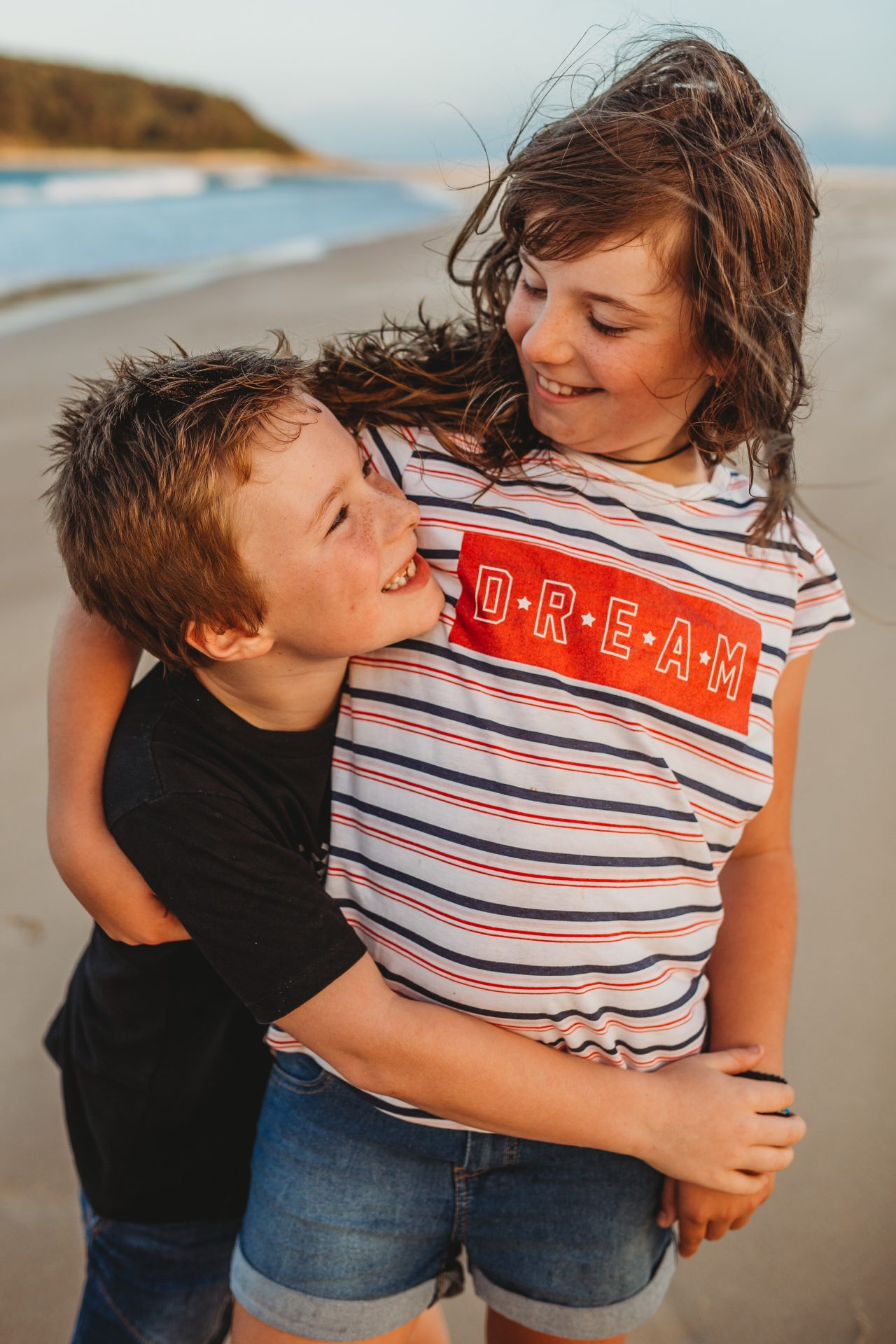 Boy hugging older sister, as they look at each other and smile