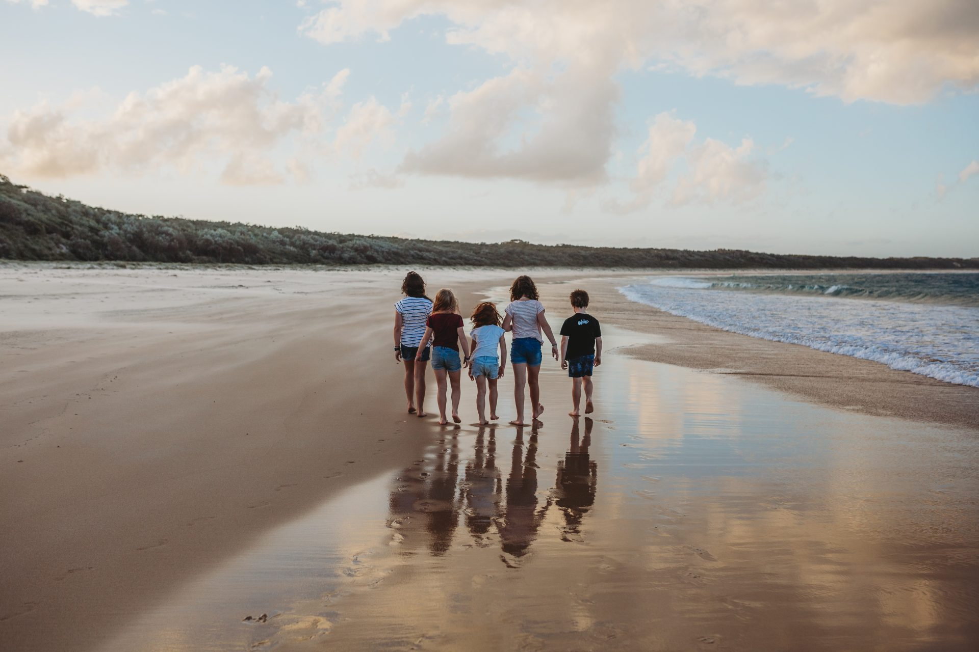 Four young girls and a boy walking along the beach at sunset