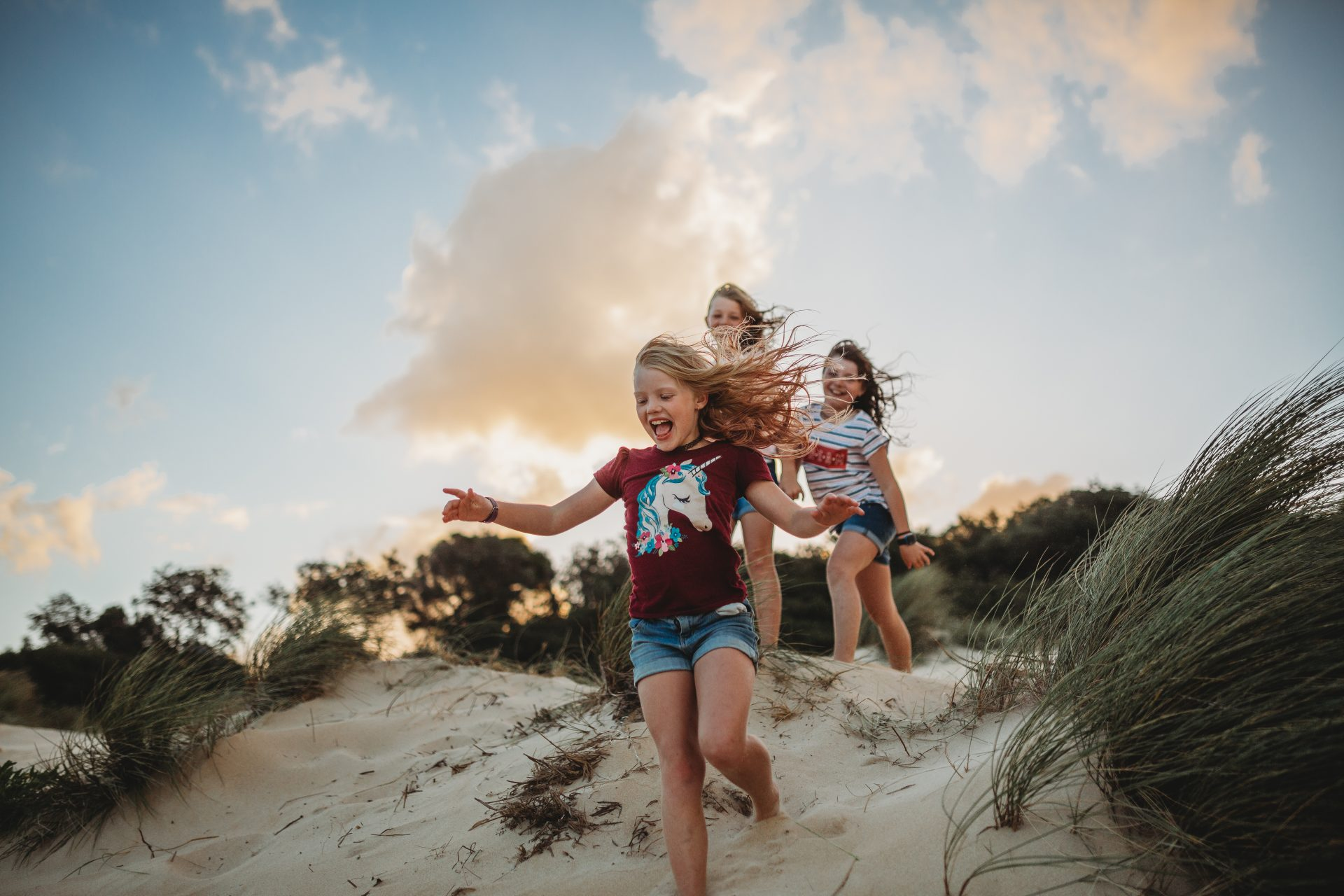 Young blonde girl runs down a sand dune, with two friends standing in the background