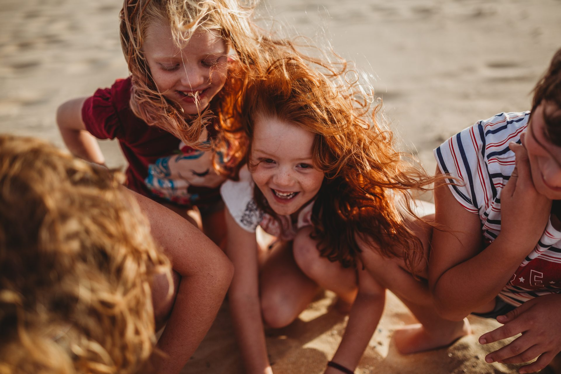 Two girls crouched down at the beach, smiling, with windy hair