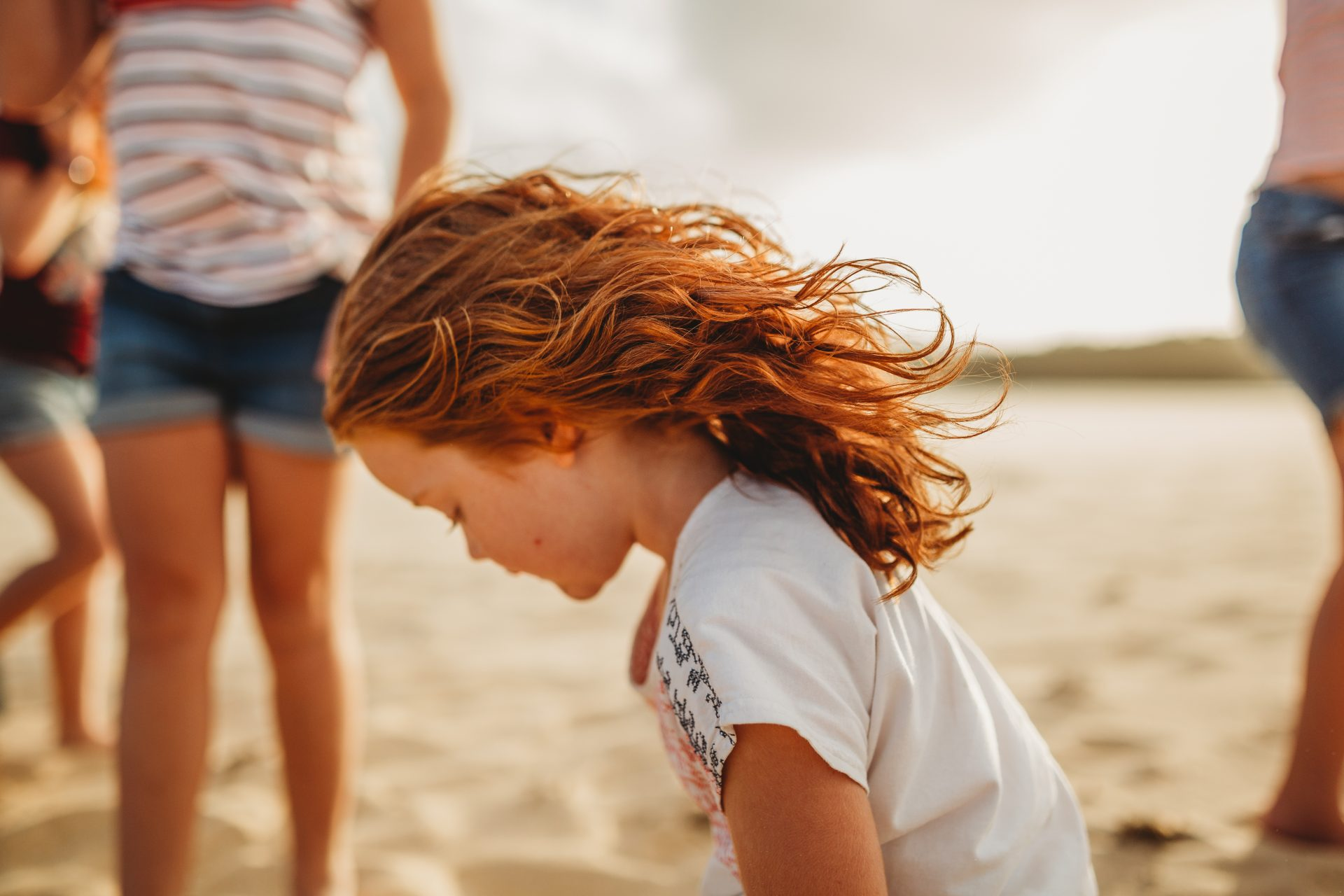 Young red headed girl at the beach with windswept hair