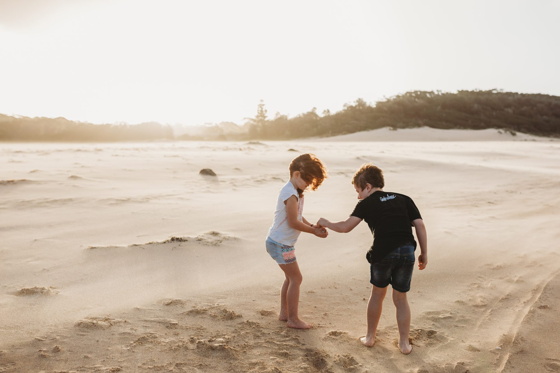 Young girl and boy collecting shells on a windy beach
