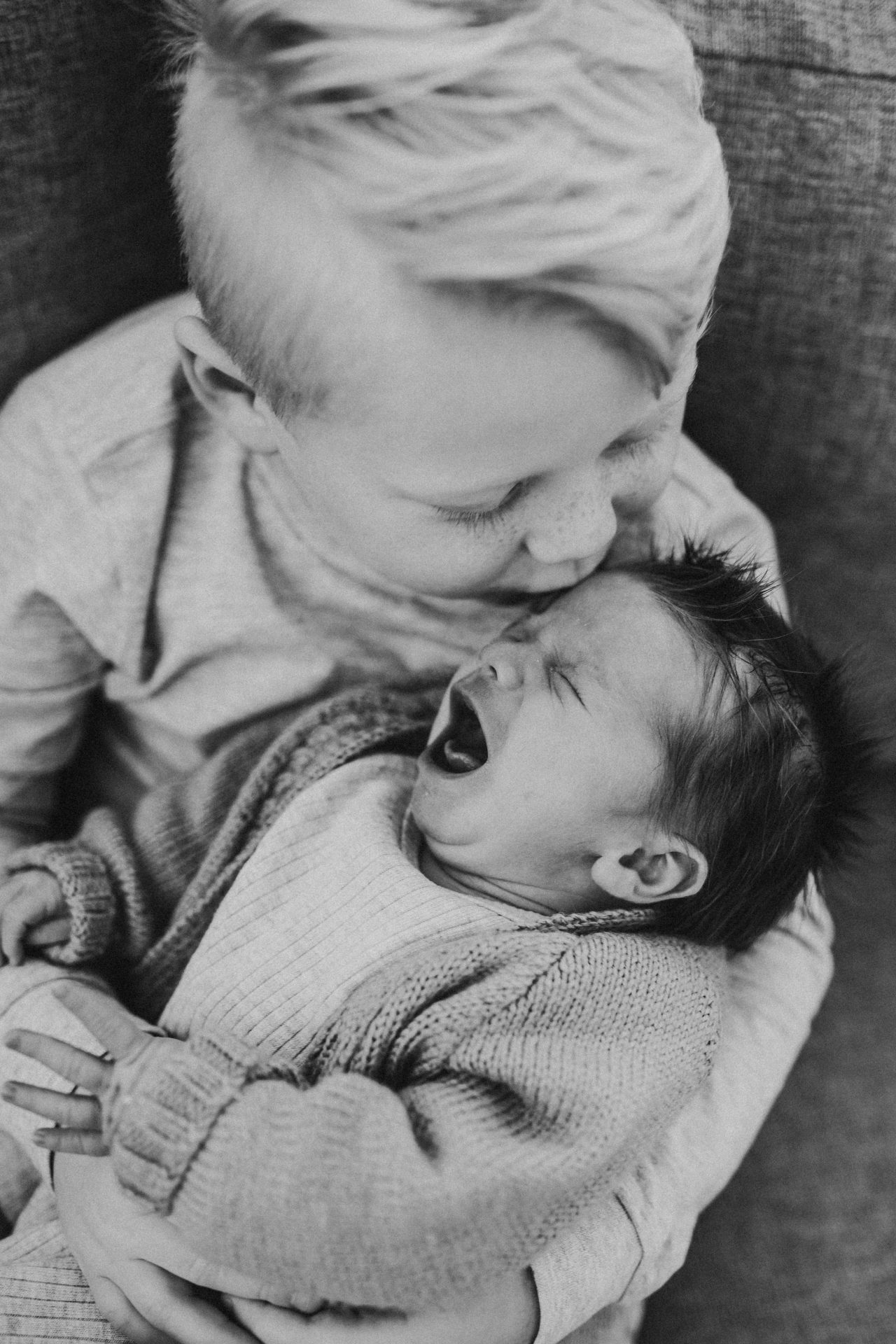 Young boy comforting his crying newborn brother
