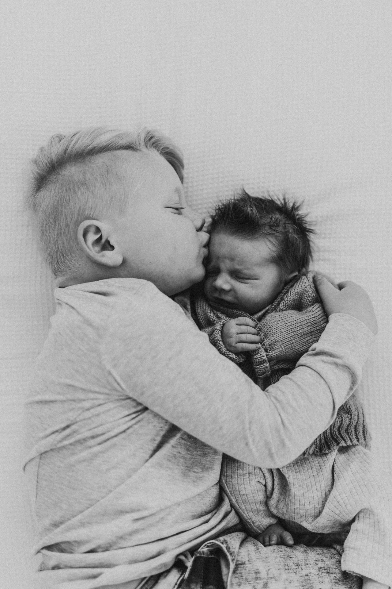 Black and white image of toddler boy hugging and kissing his newborn baby brother
