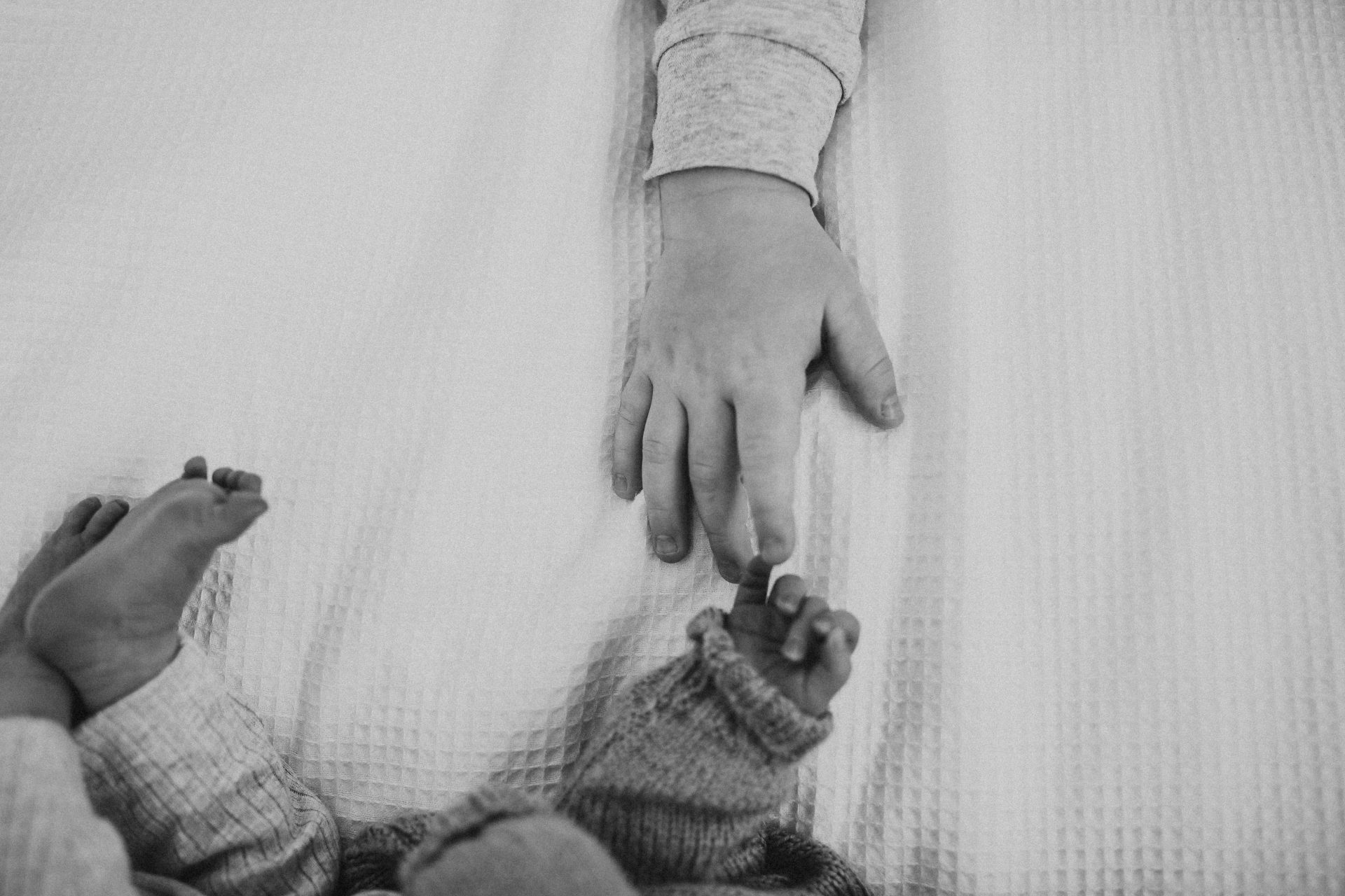 Boy's hand reaching out to newborn baby's hand