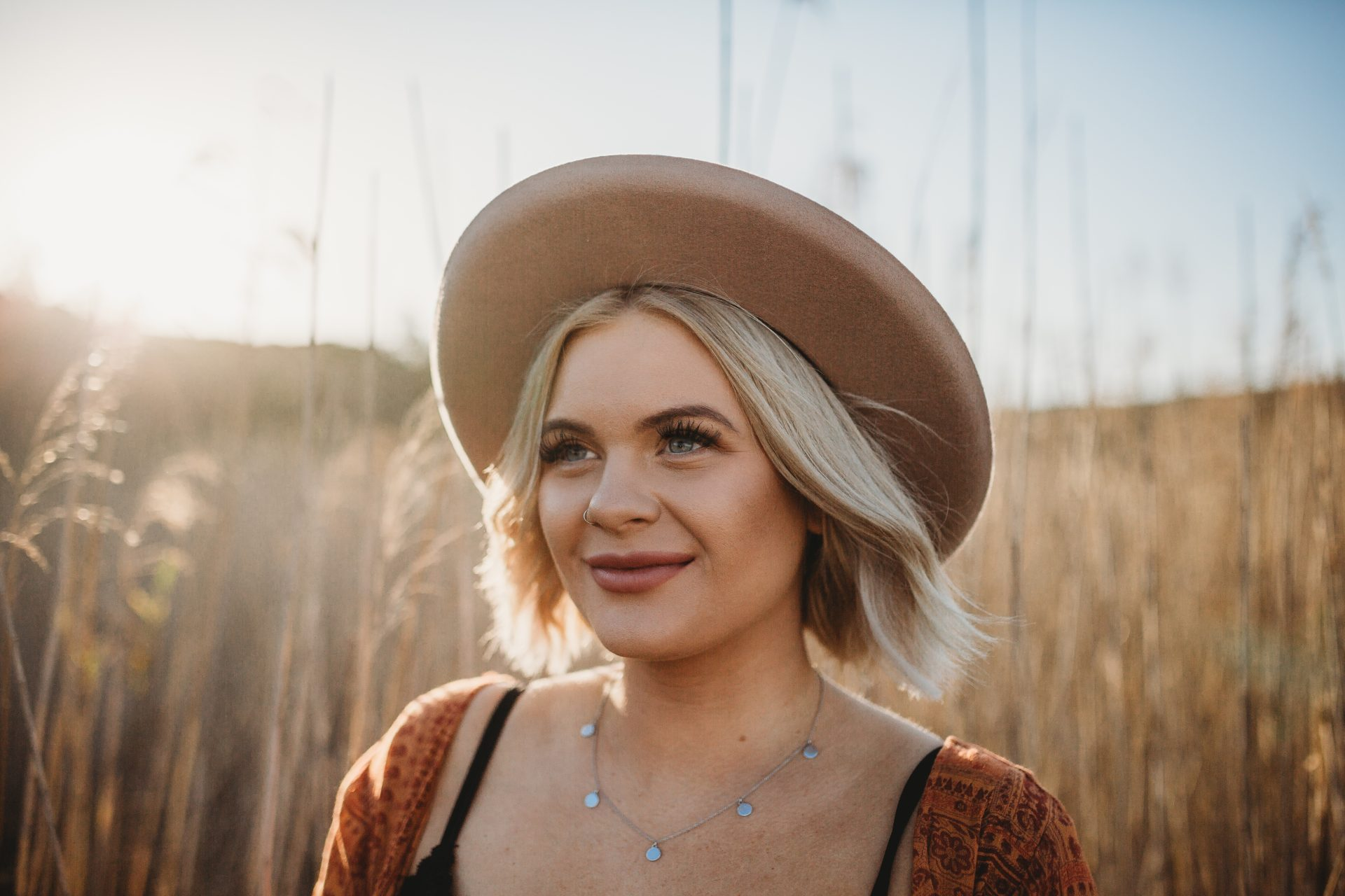 Blonde girl wearing Lack of Colour hat, looking off into the distance