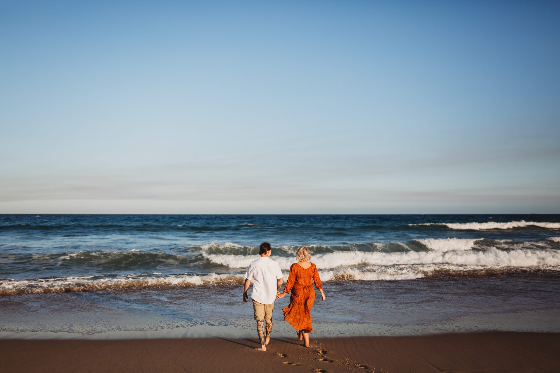 Young couple walking into the ocean at sunset, while holding hands
