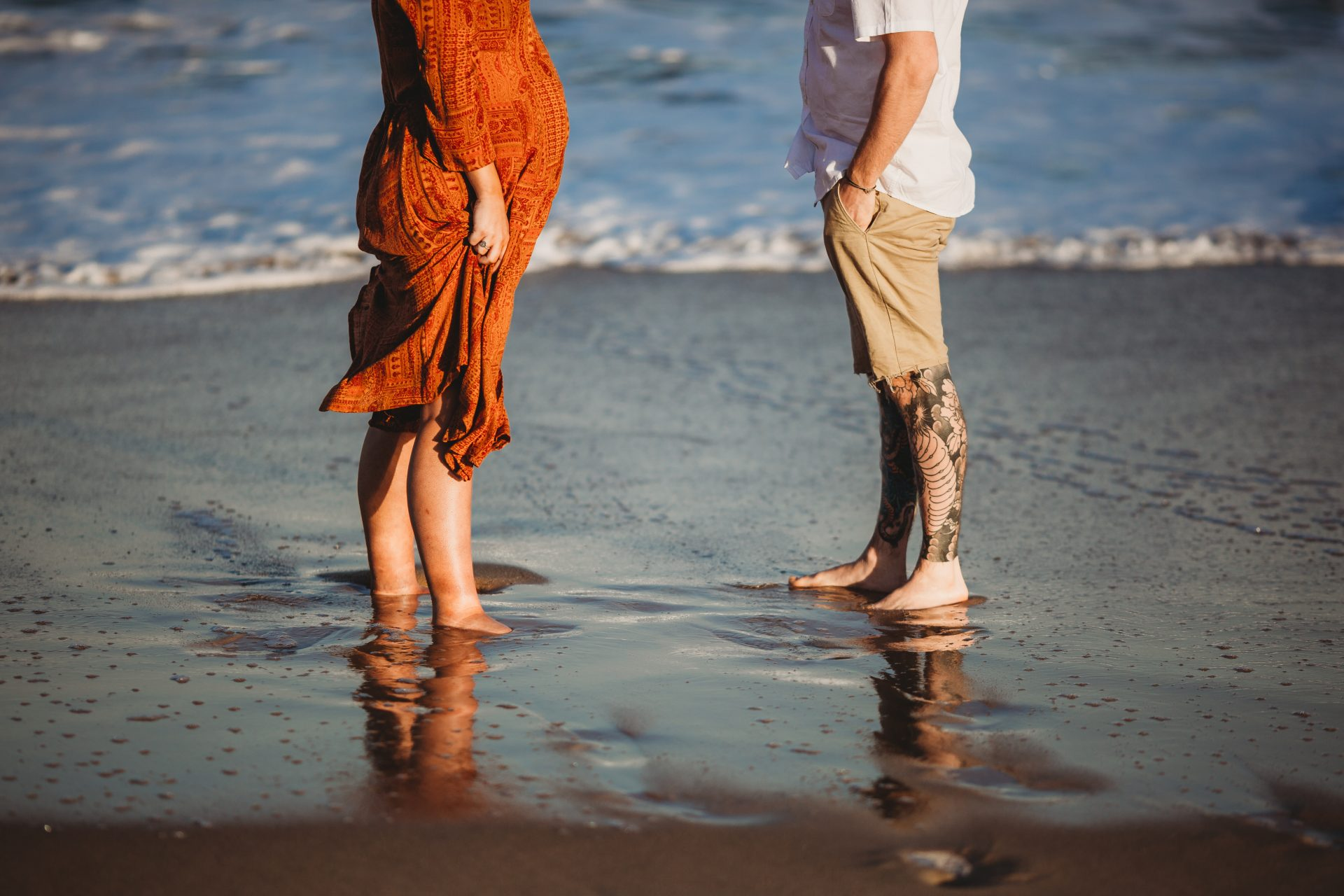 Young couple standing in the wet sand, facing each other