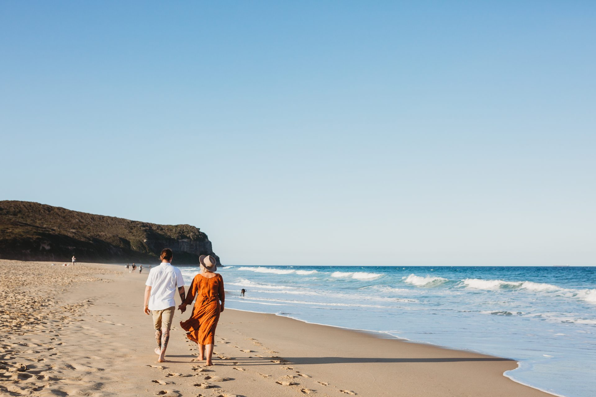 Young man and woman walking on the beach, away from the camera