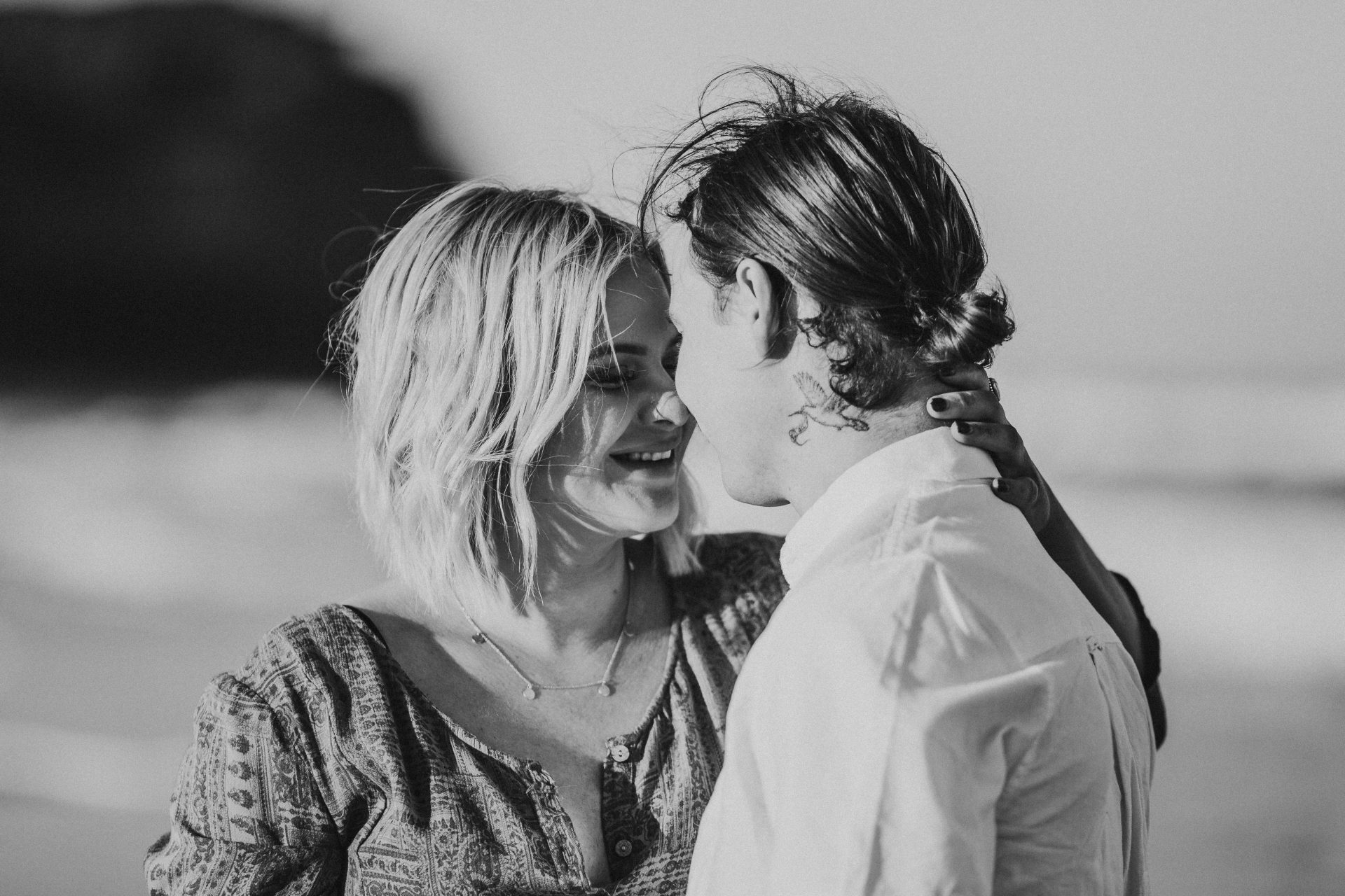 Black and white image of couple caressing at maternity session at Dudley Beach at sunset