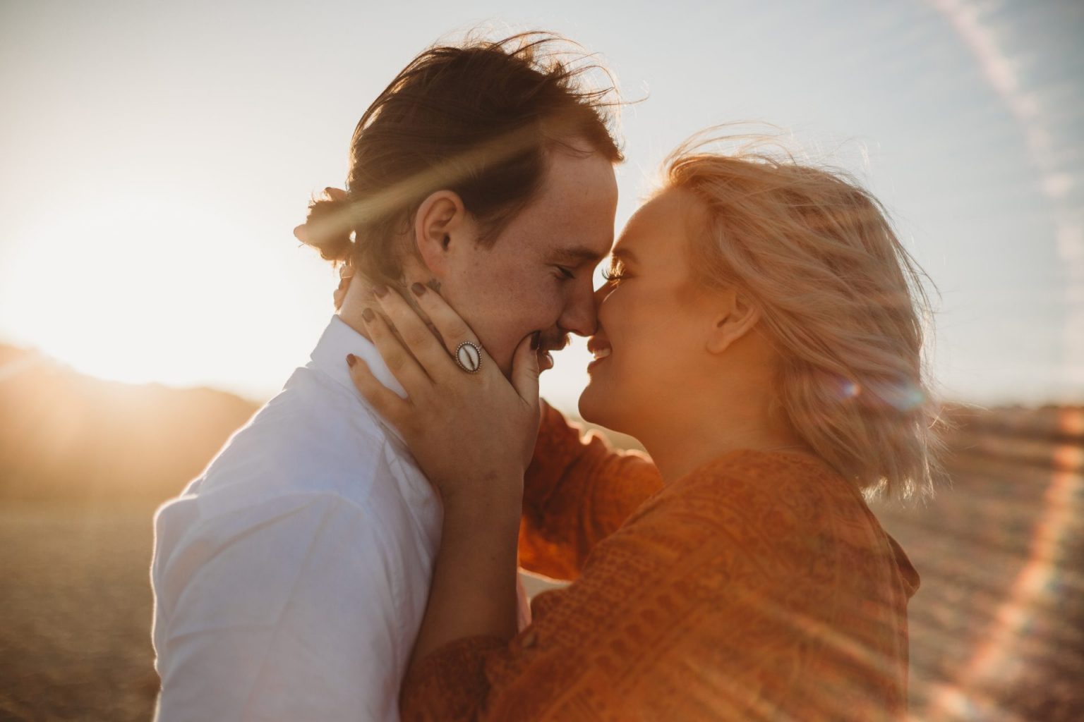 Young couple in an embrace, woman with her hand on her boyfriend's cheek, surrounded by sun flare at sunset
