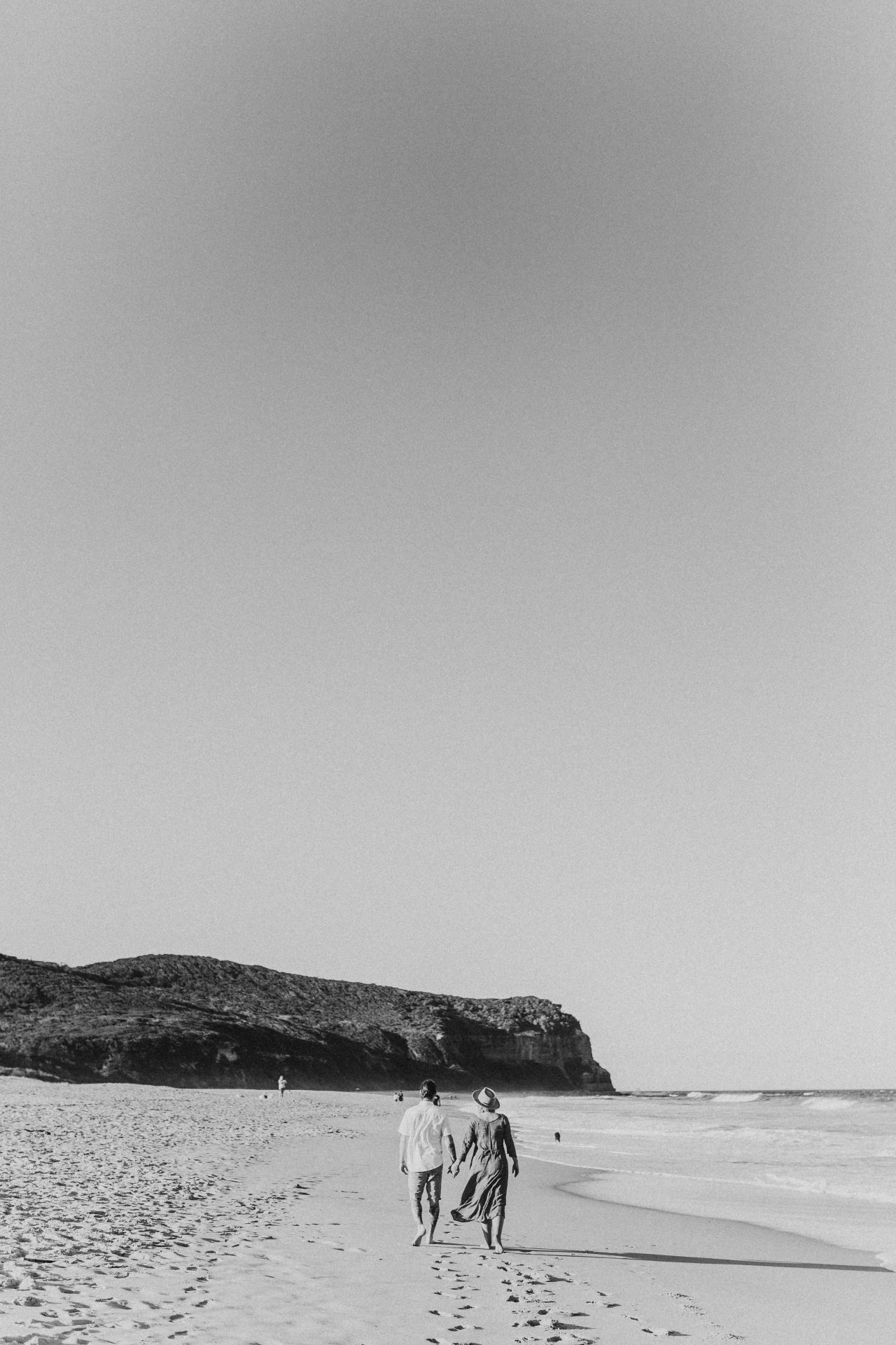 Black and white image of young couple walking away on the beach