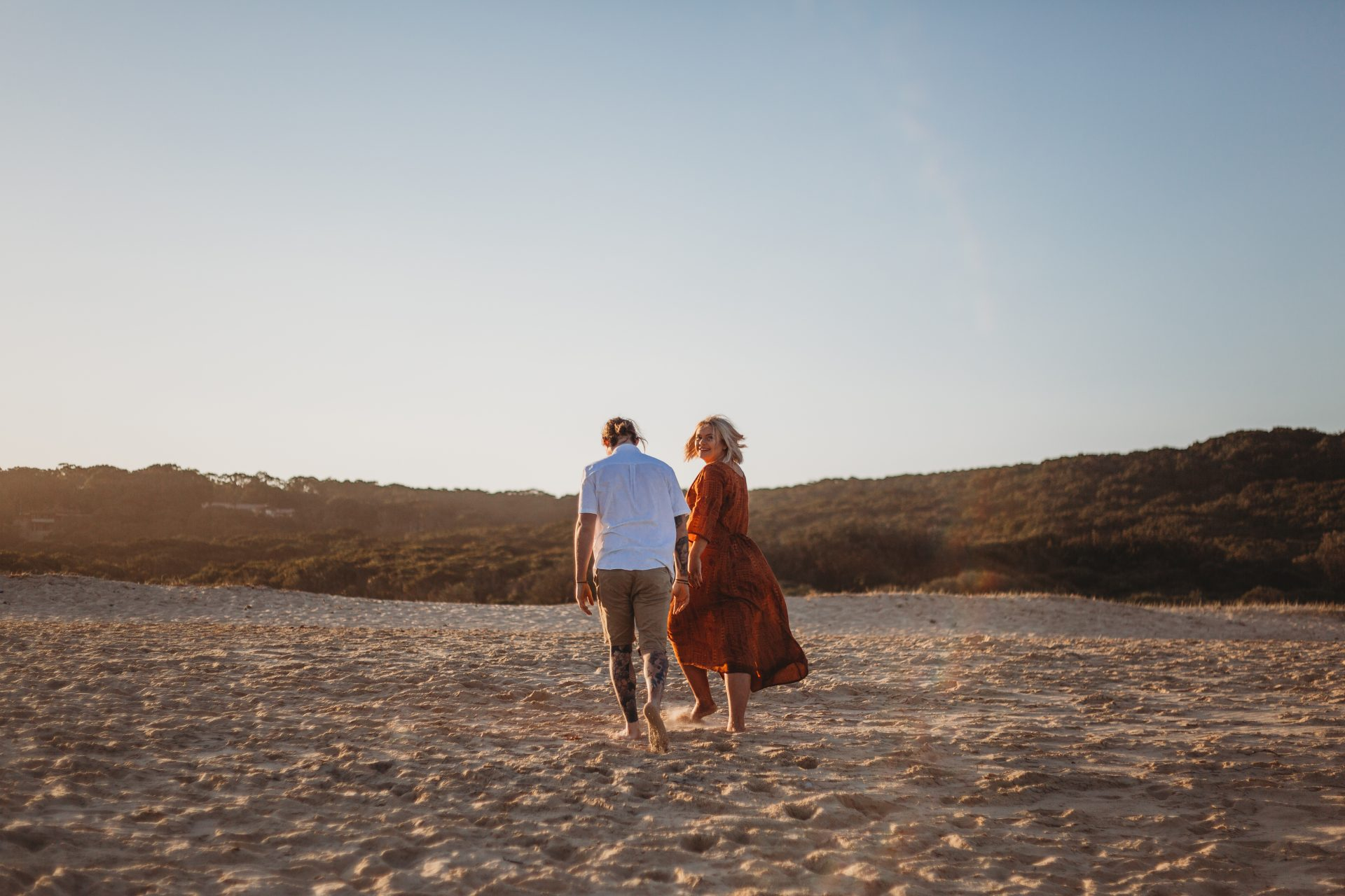 Young boho couple walking along the sand at the beach