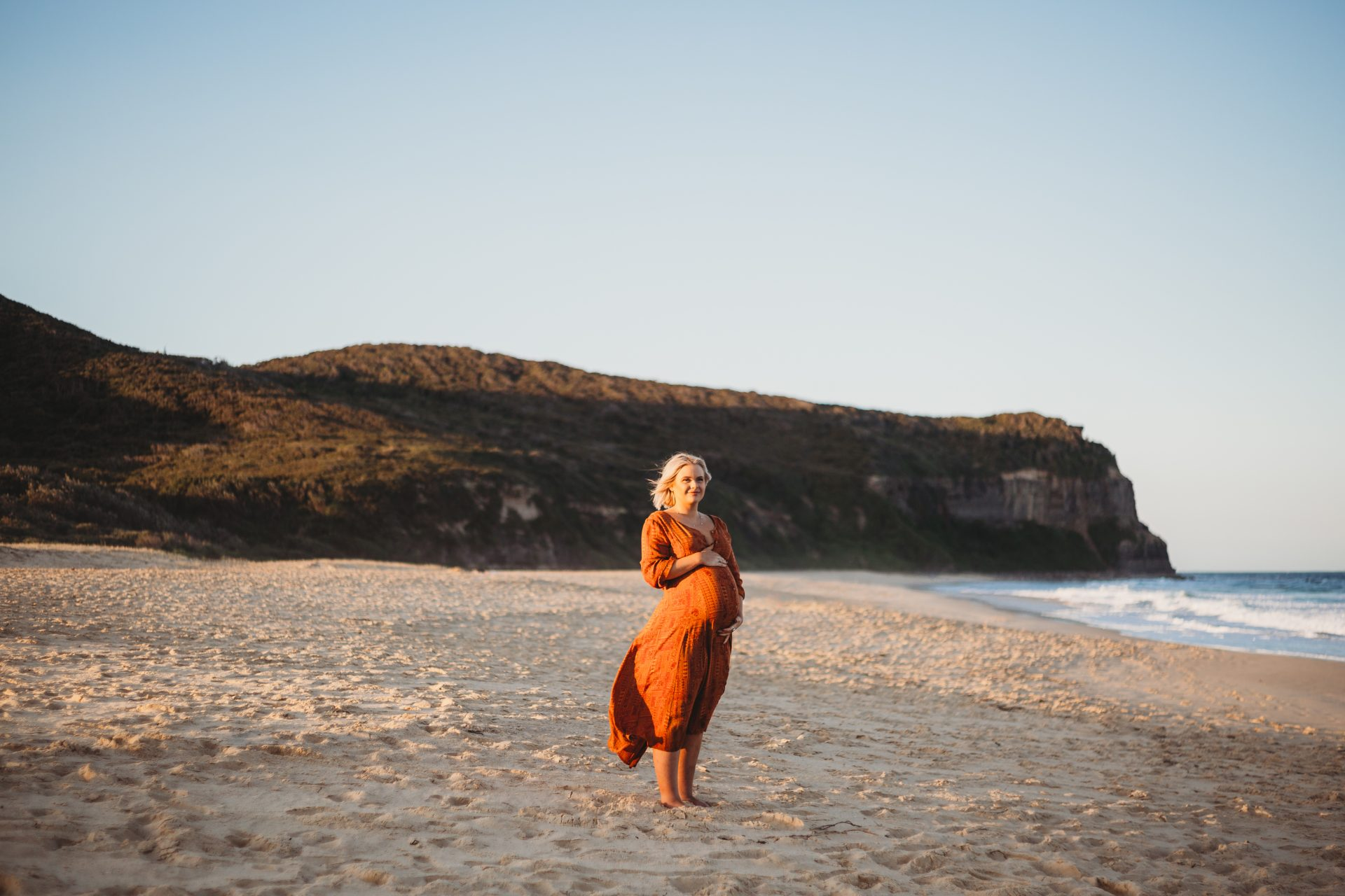 Young blonde woman smiling while holding her pregnant stomach, on Dudley Beach at sunset