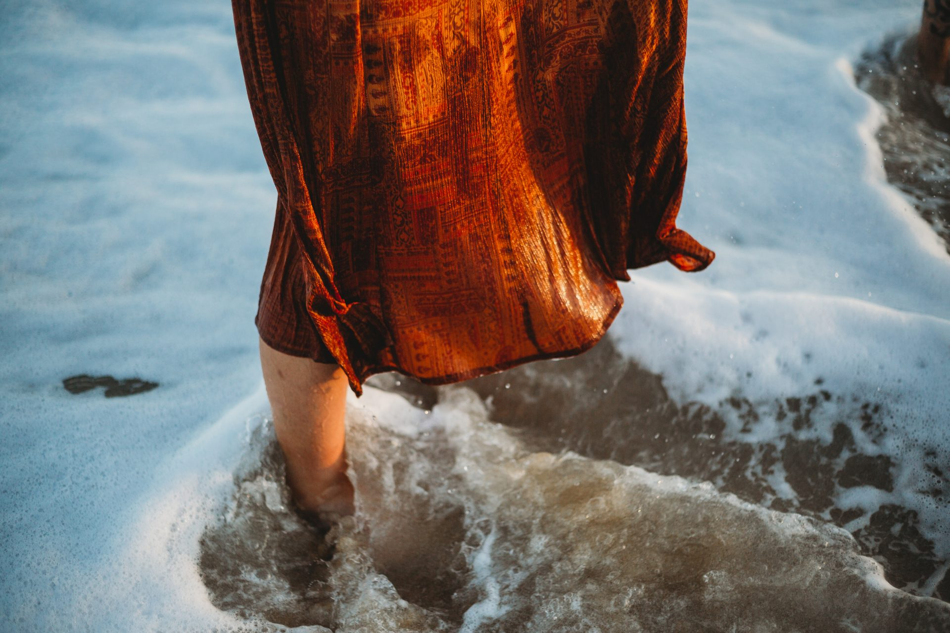 A woman's feet in the water at the beach as her orange dress floats in the wind around her ankles
