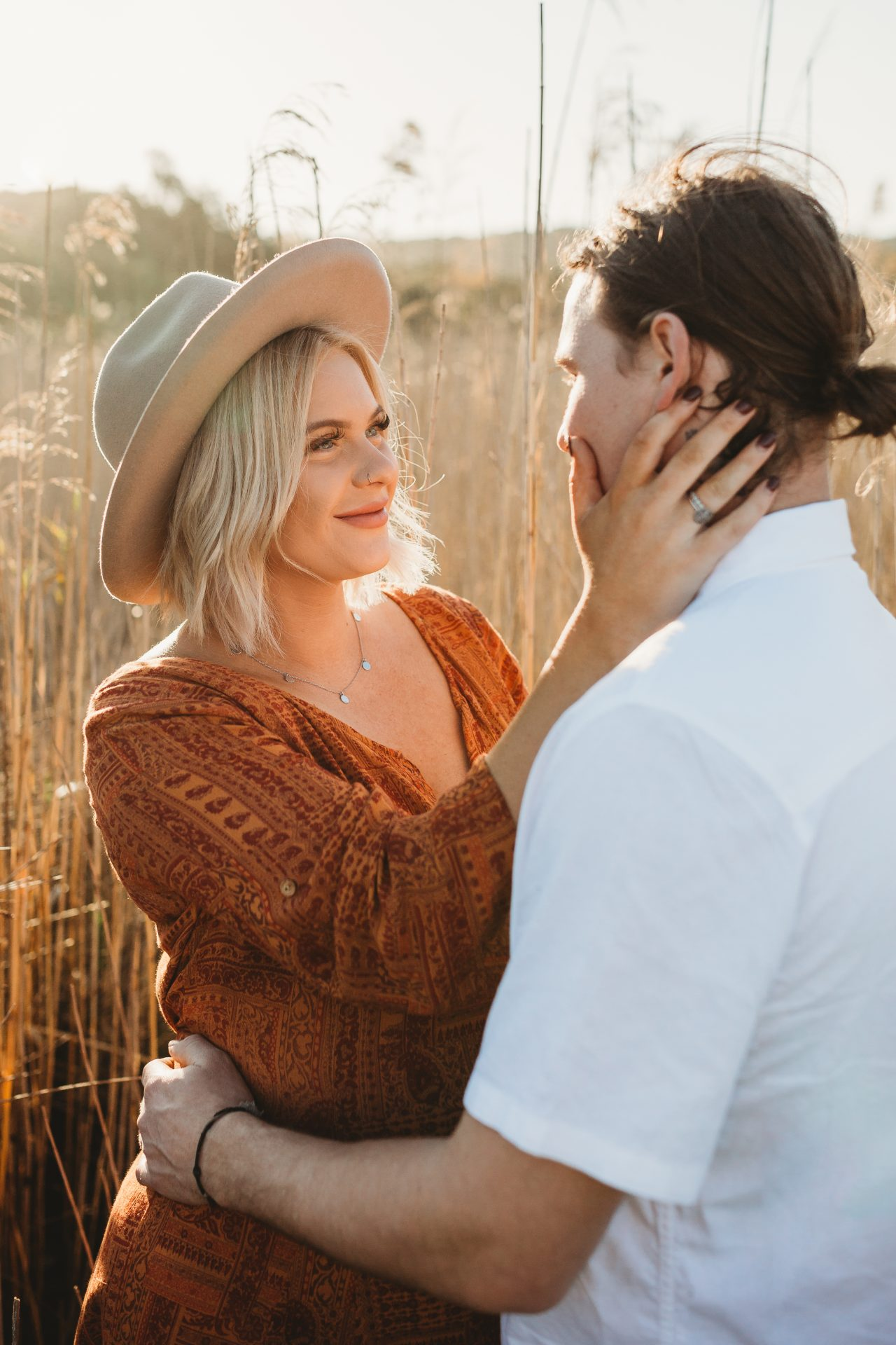 Young boho woman in wide brimmed hat, caresses her boyfriend's face while smiling at him