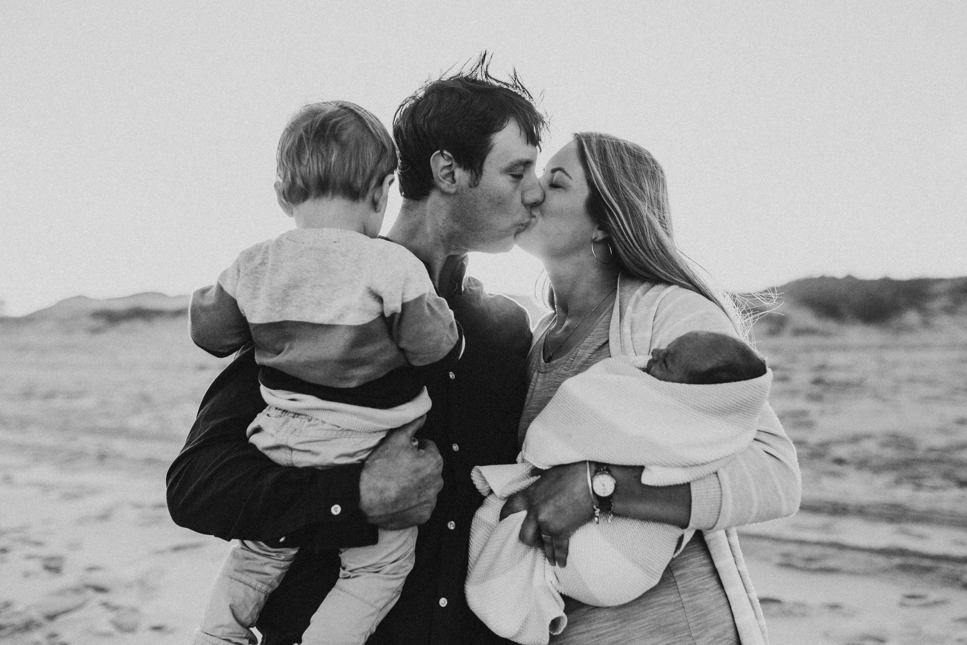 Black and white image of couple kissing while holding their daughter and son