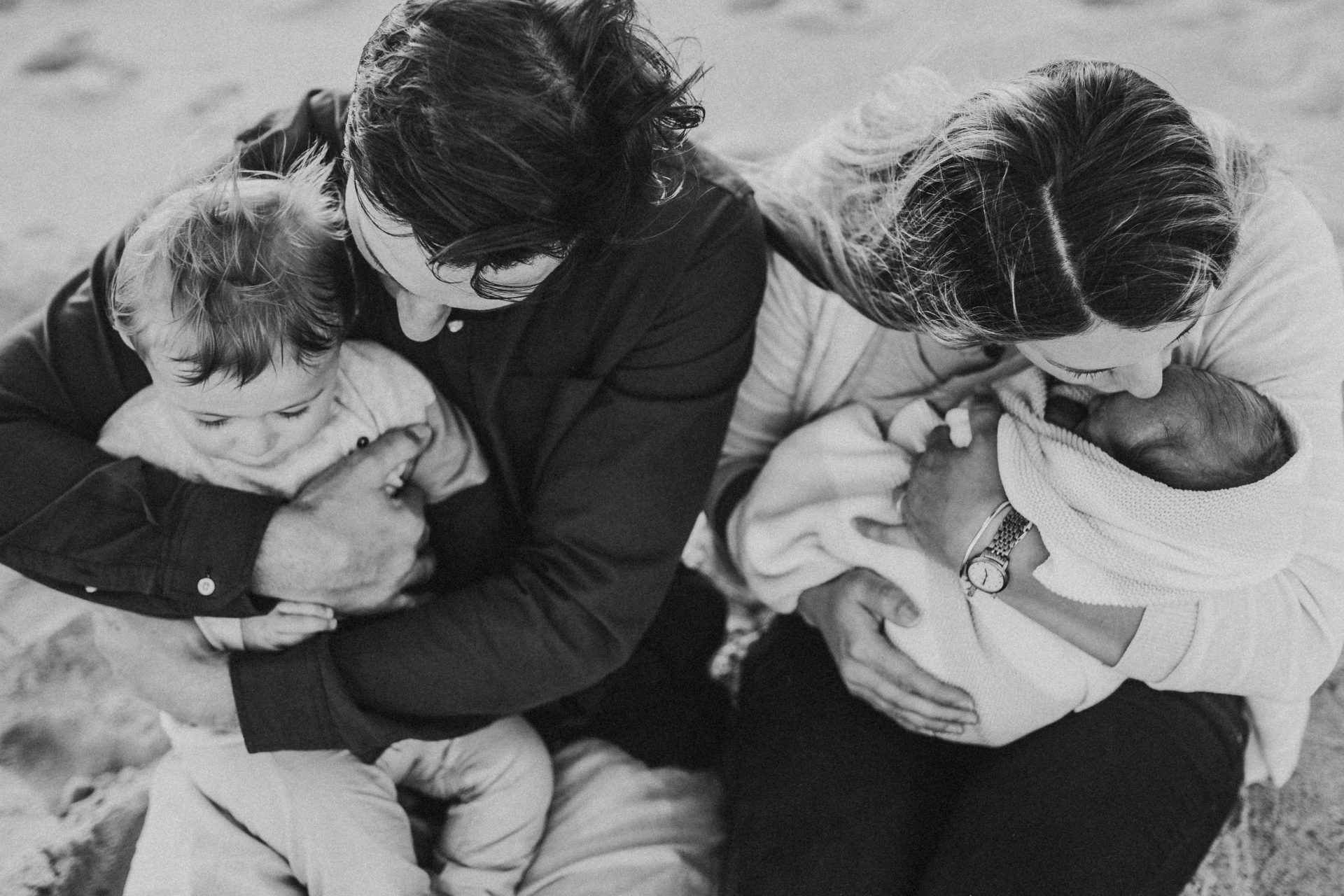 Black and white image from above of mother and father cuddling toddler and baby