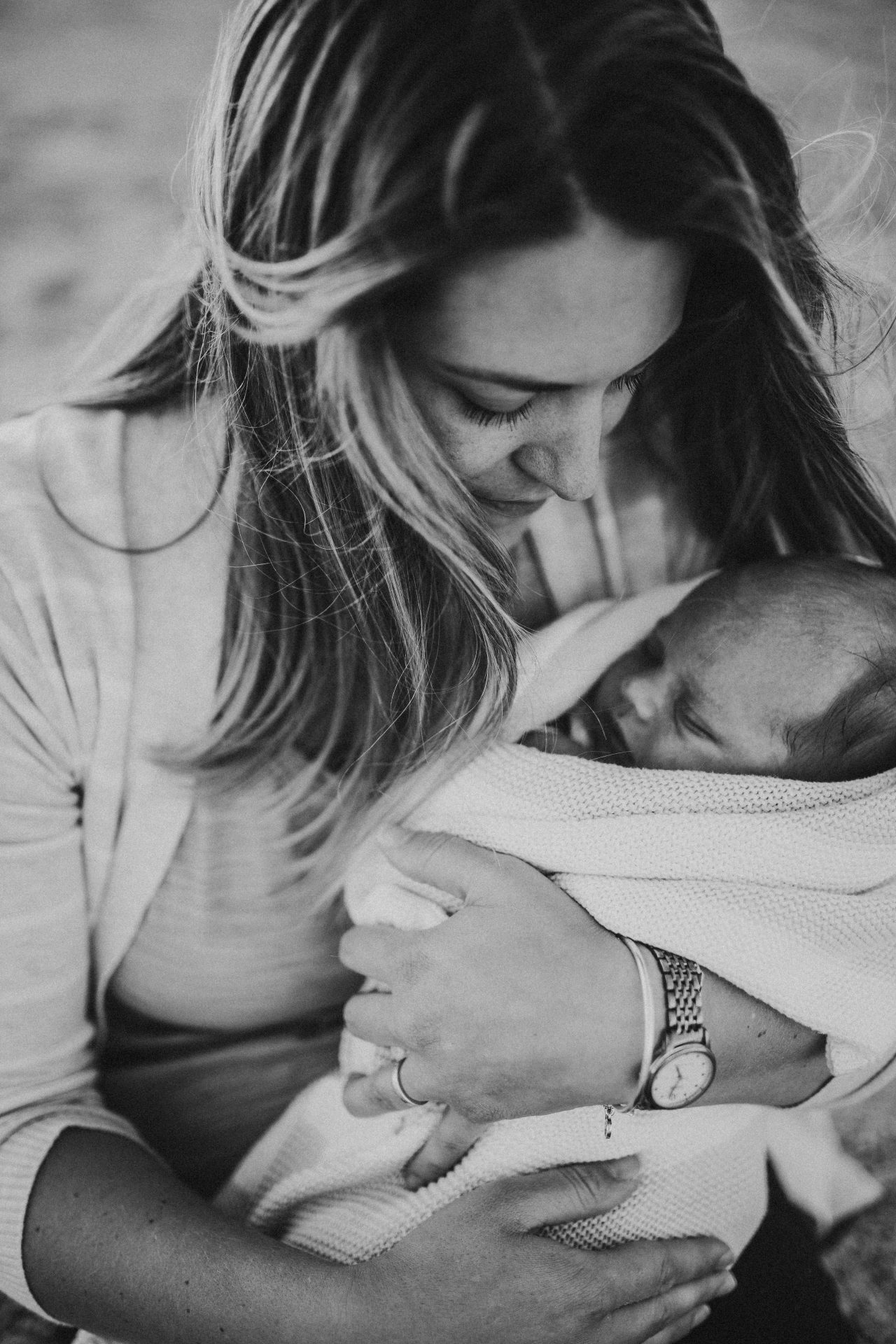 Black and white image of mother holding her baby girl close