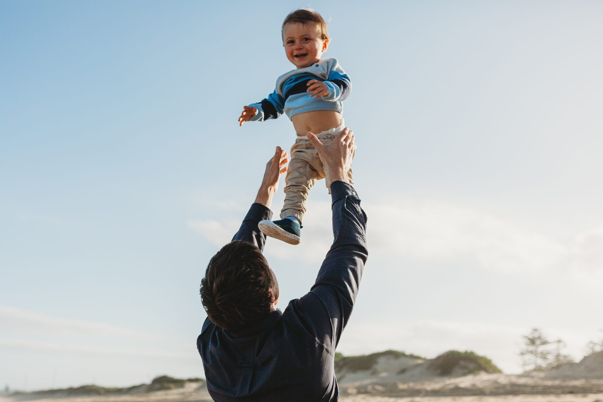 Father playfully tosses toddler into the air