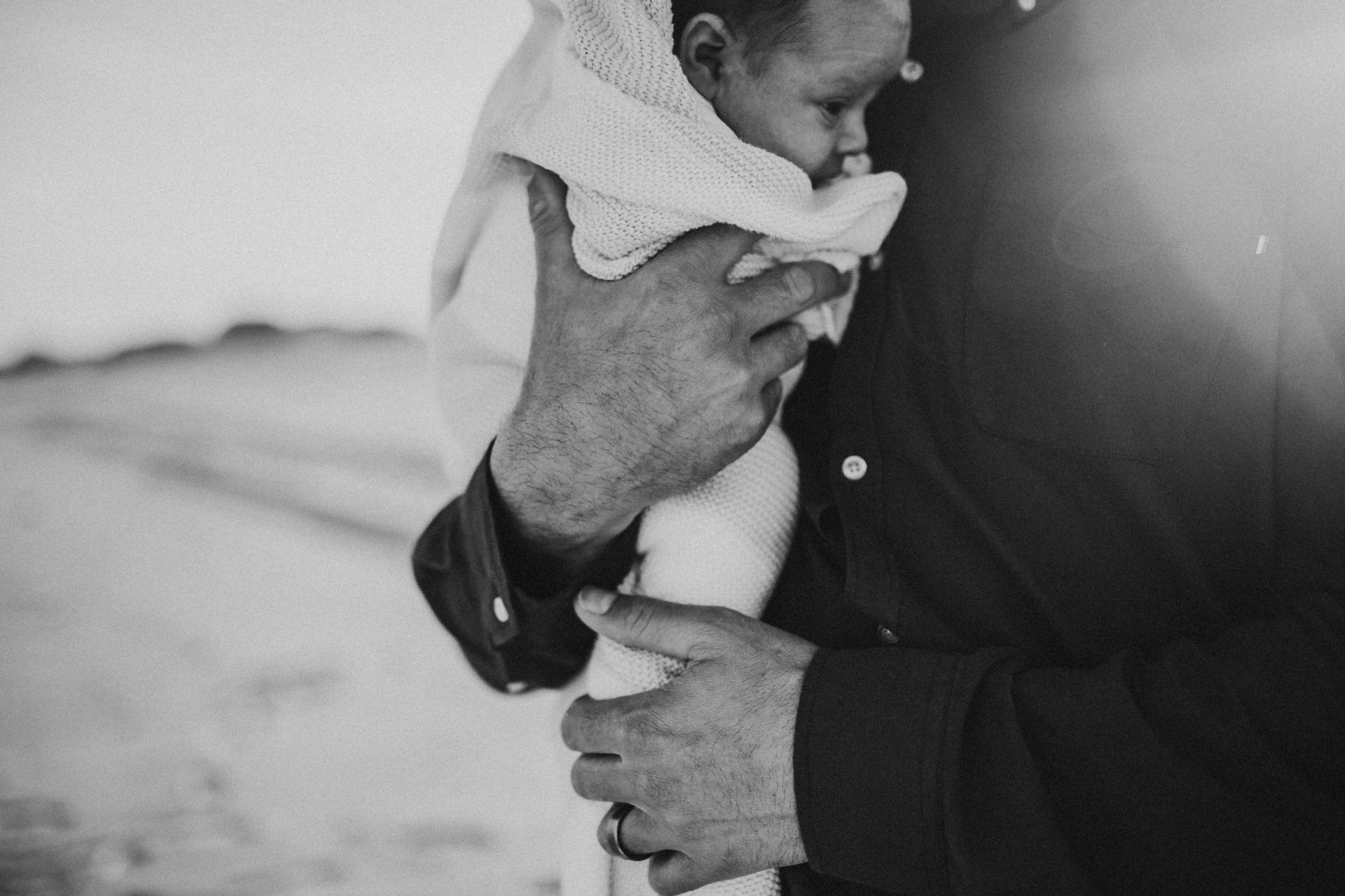 Black and white close up of man's hands cradling his baby girl