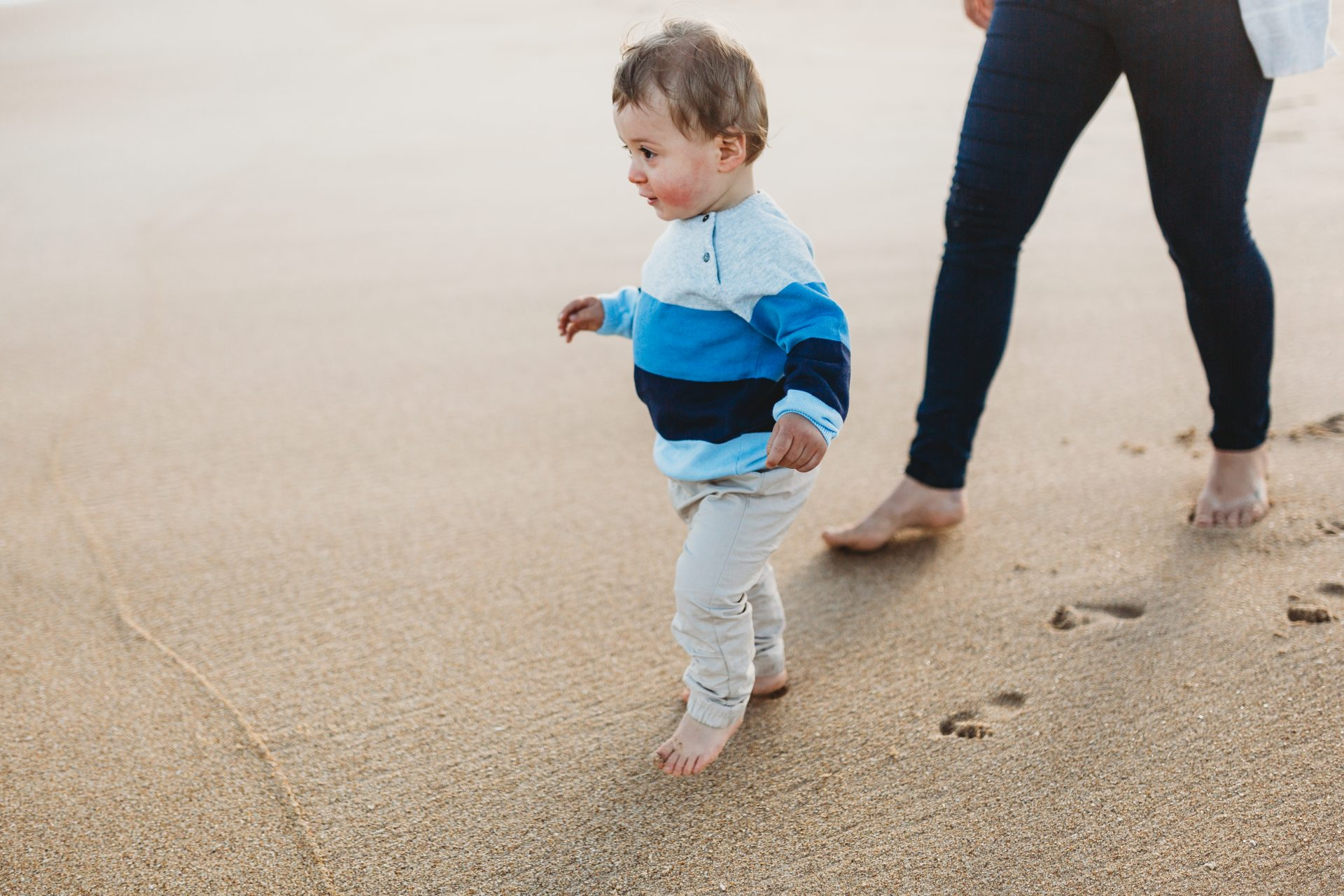 Toddler taking steps away from his mother at the beach