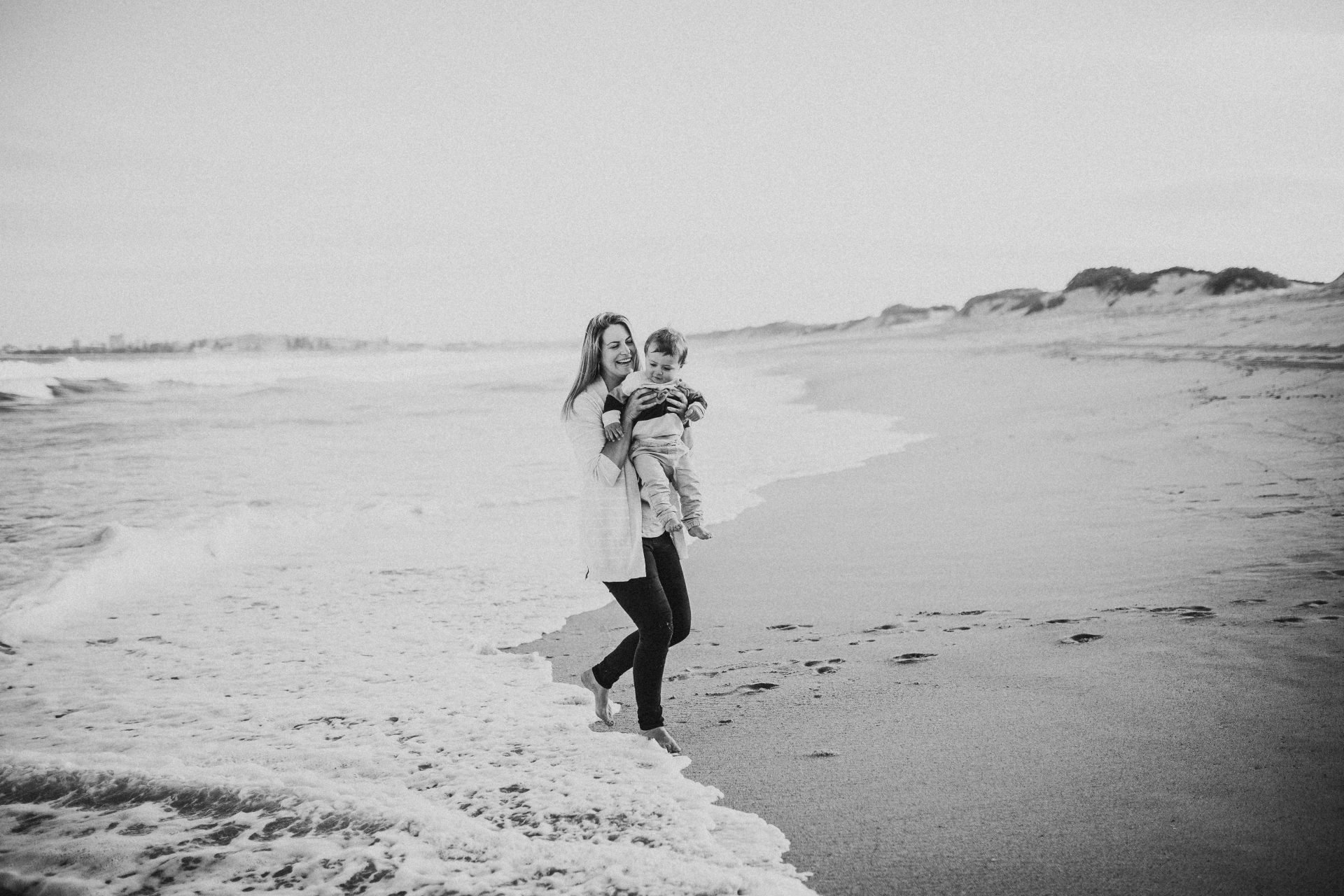 Black and white image of a woman with her toddler son on the beach, at the edge of the water