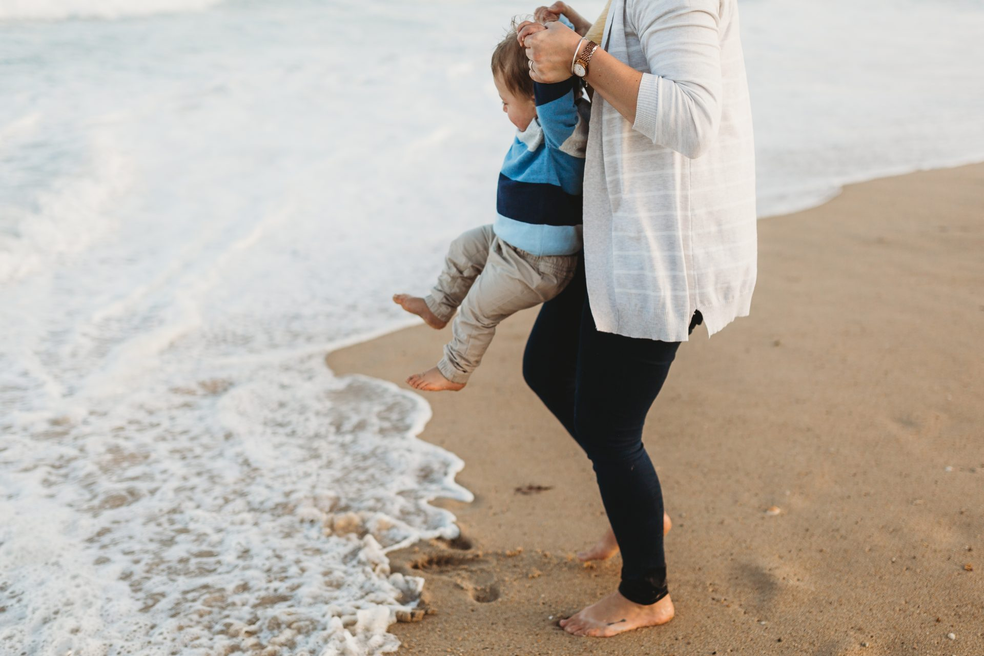 Woman lifting her toddler up out of the way of the water at the beach