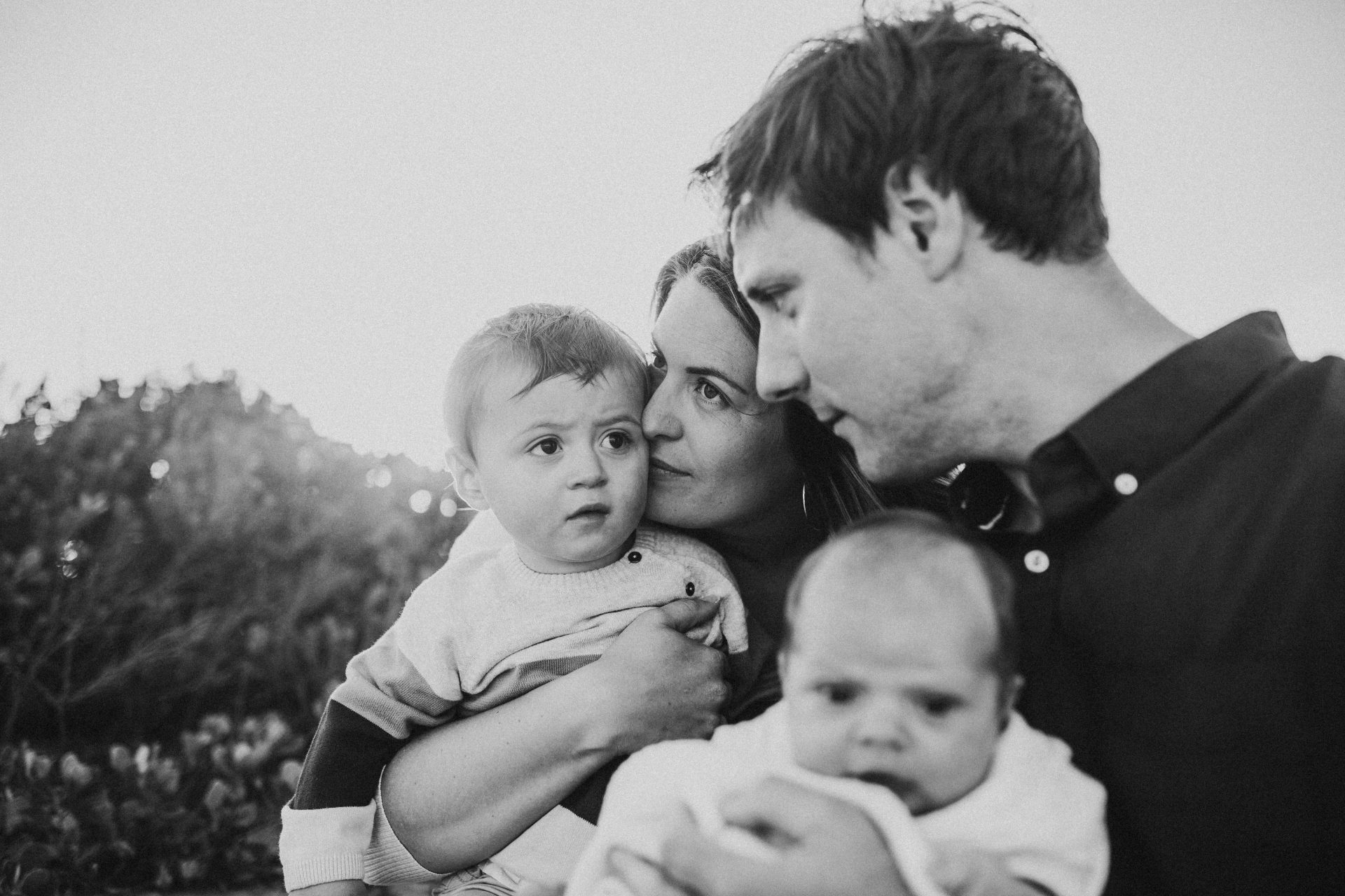 Black and white group shot of young family cuddled together during lifestyle photography session