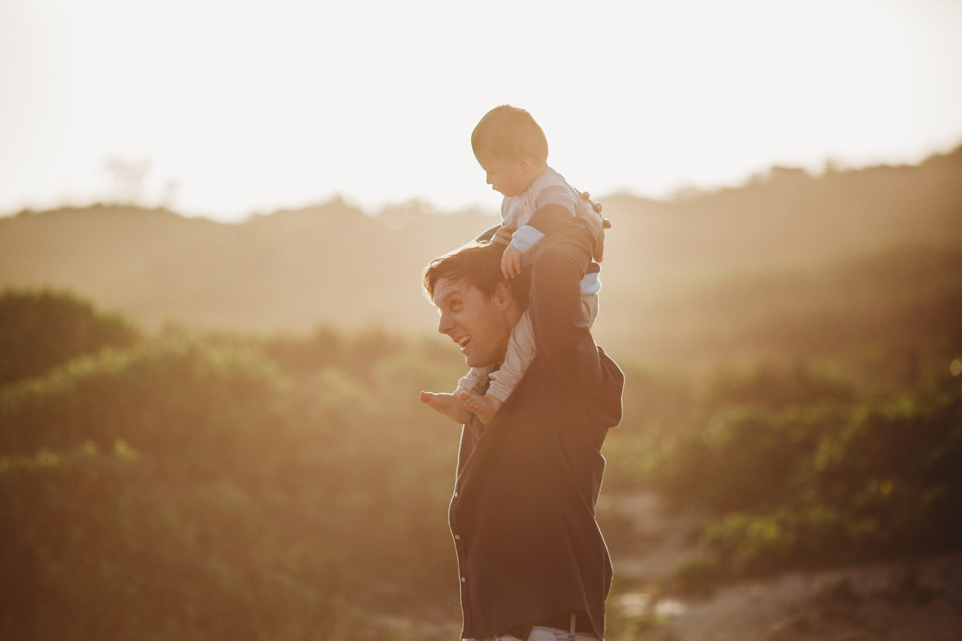 Toddler boy rides on his dad's shoulders at sunset on the beach