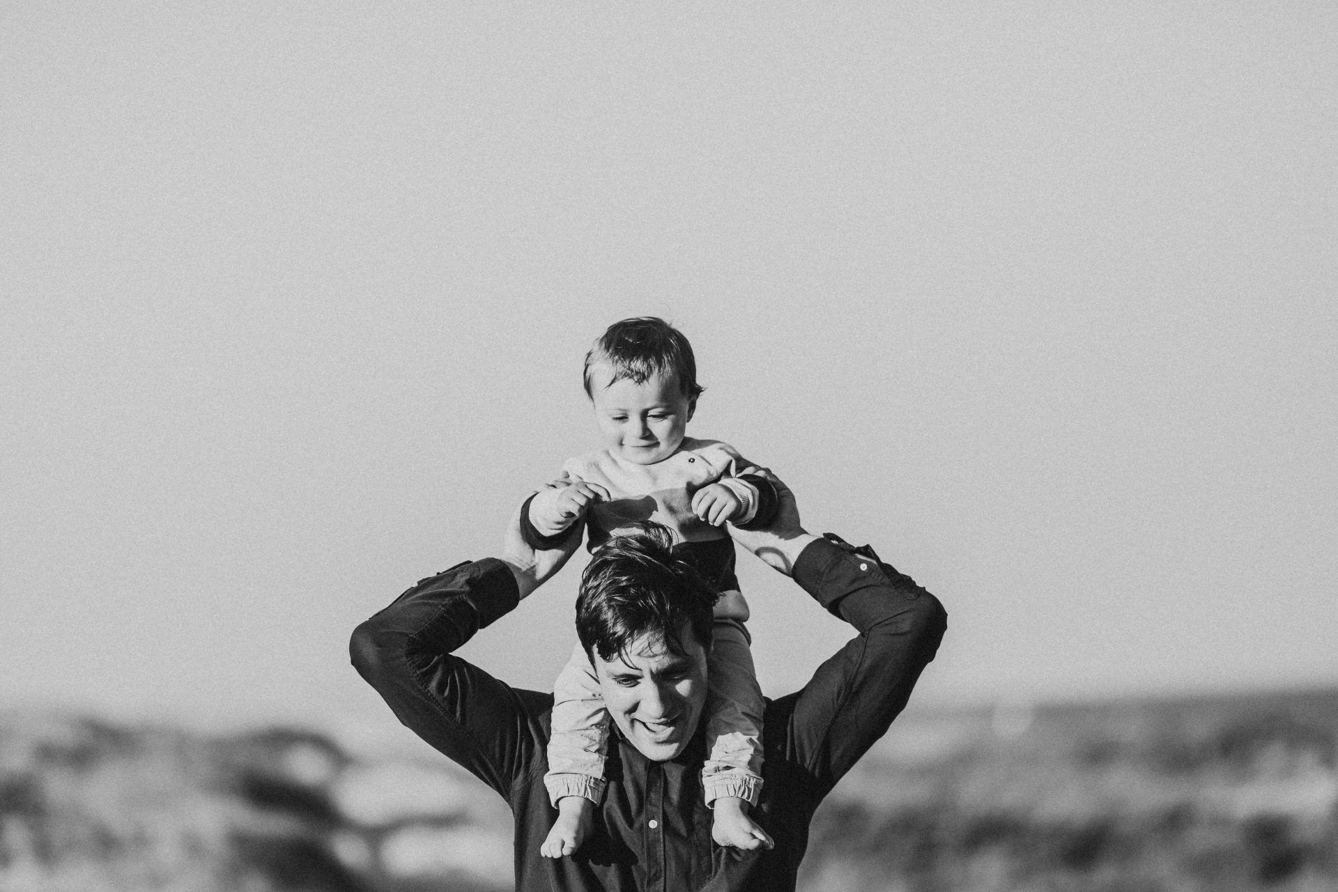 Black and white image of toddler on his father's shoulders