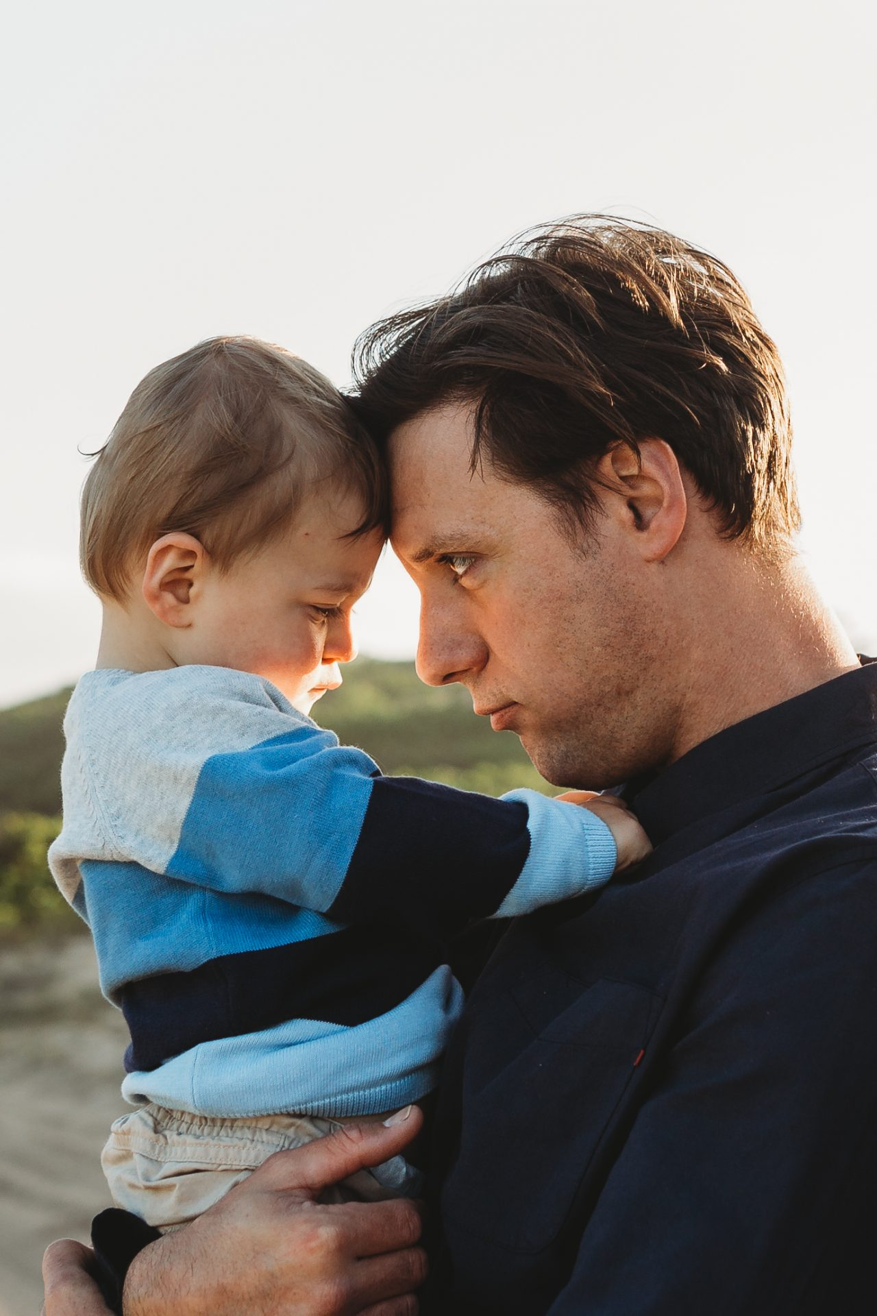 Father and toddler touching foreheads with father imitating toddler's pout
