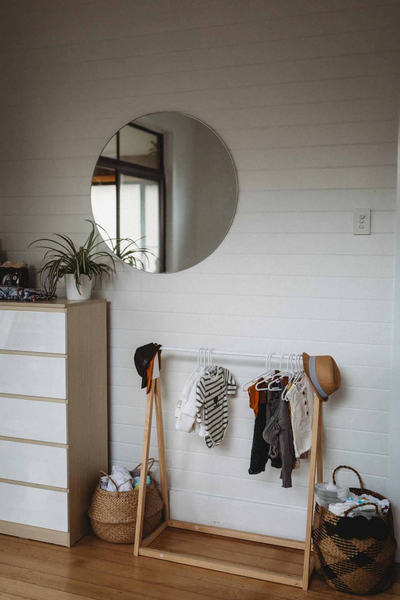 Mini clothes rack with baby clothes hanging on it, with a circular mirror on the wall above