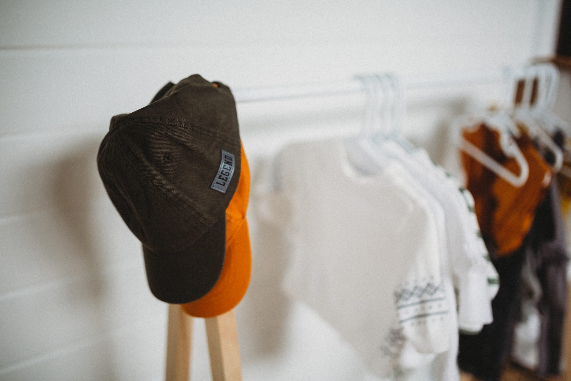 Close up of hats and shirts hanging on child's clothes rack