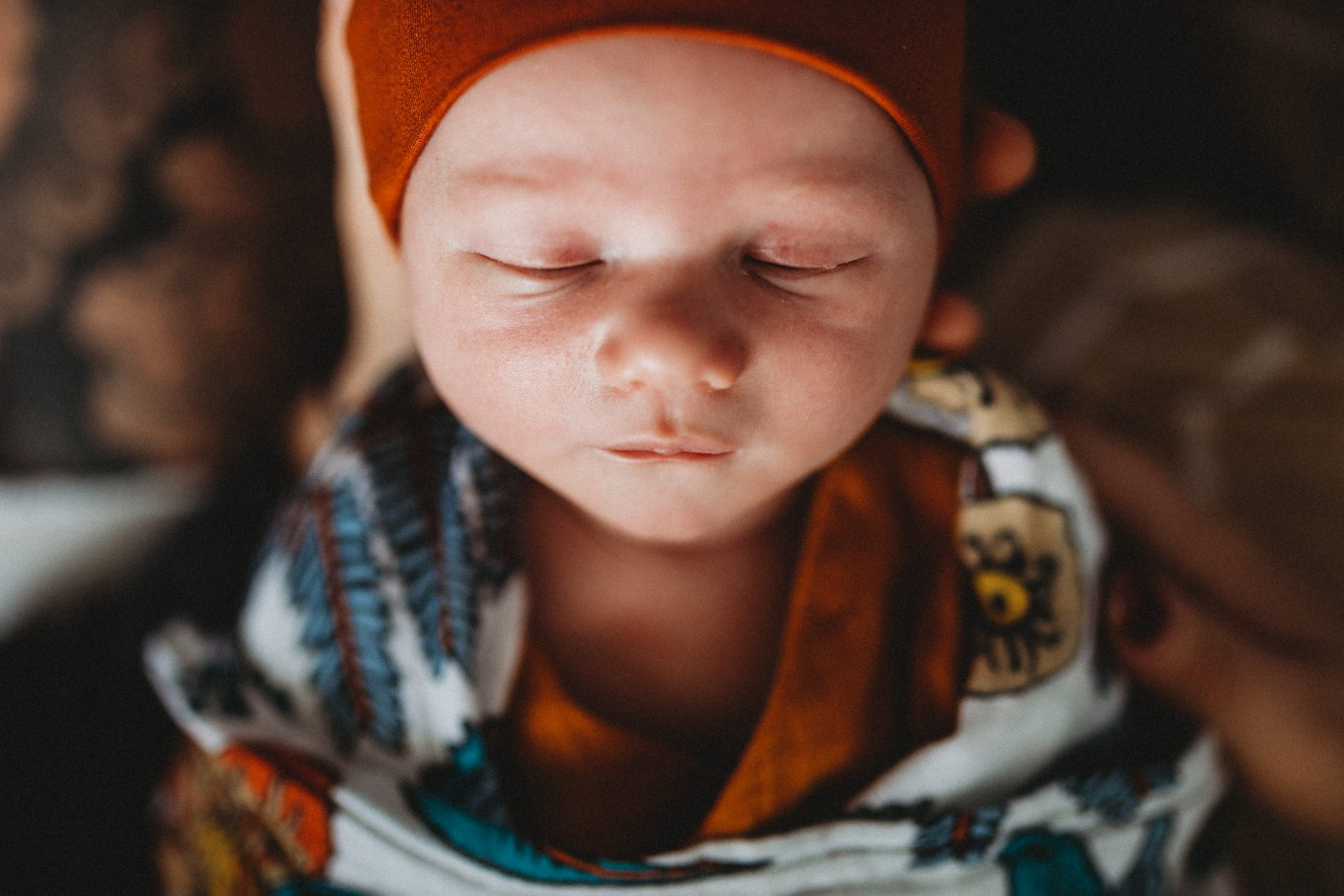 Close up of sleeping baby's face, being held by his father. Wearing dark orange beanie and floral muslin wrap.