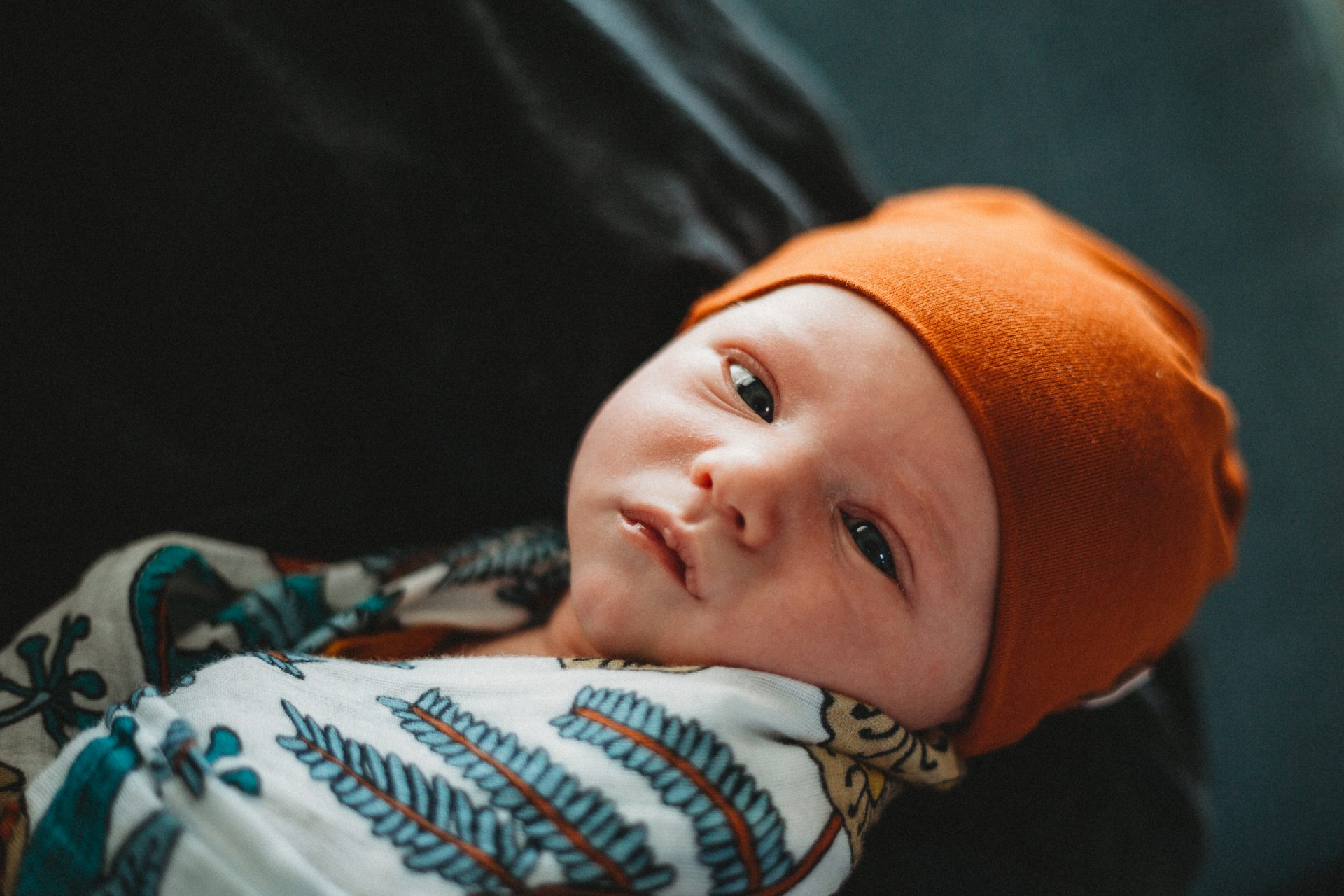 Newborn baby boy in his father's arms, turned to look at camera