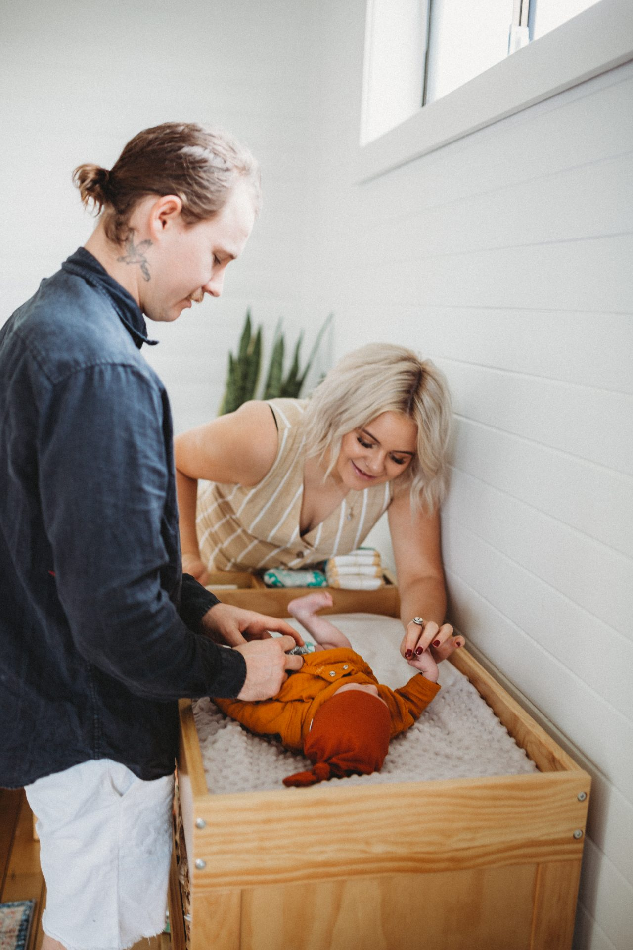 Young parents changing baby's nappy at change table