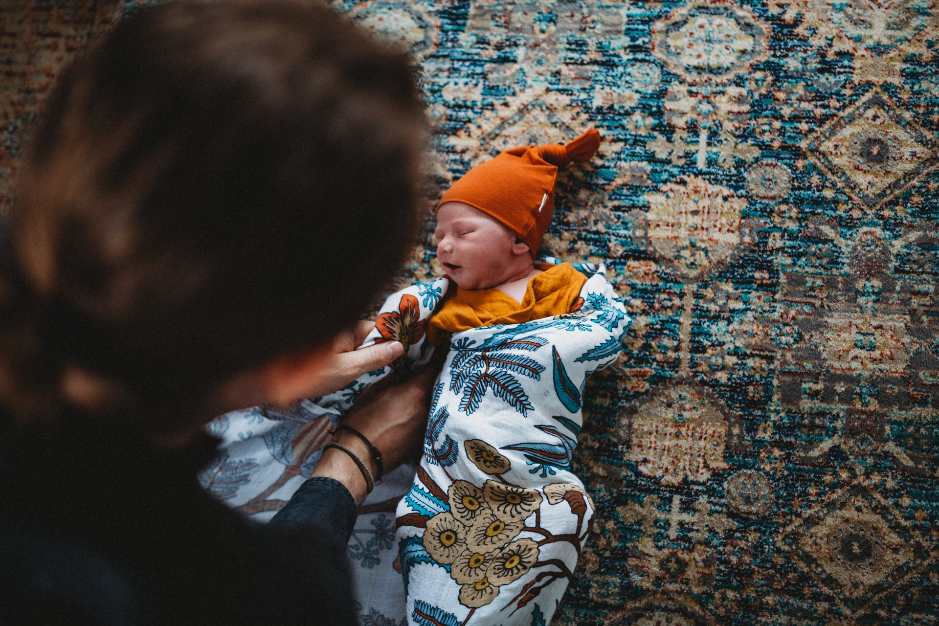 Young father wrapping baby son, on a colourful rug on the floor