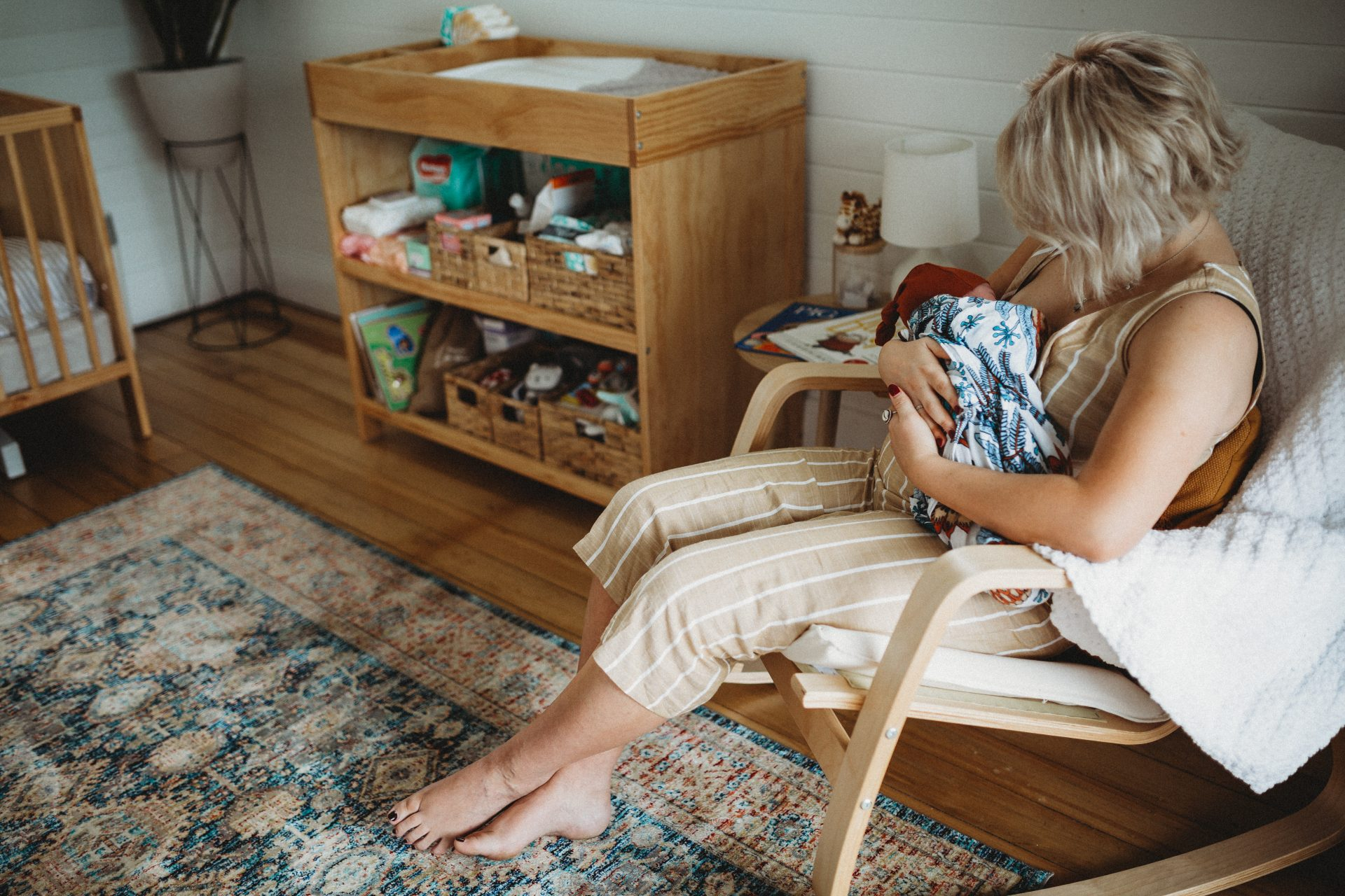 Young mother in rocking chair holding baby. Newcastle newborn photographer