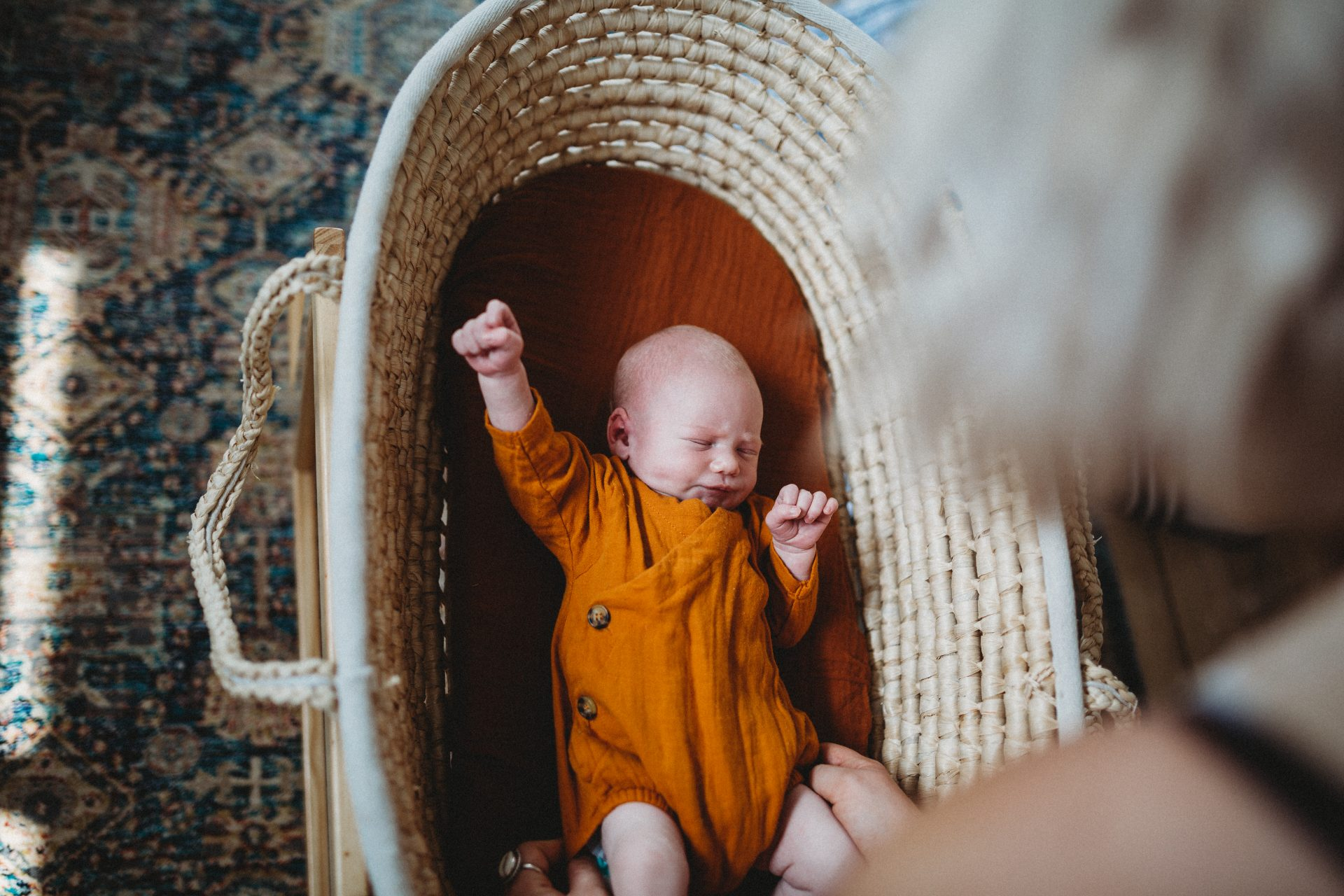 Baby in wicker basket, appearing to be fist pumping the sky, as mother looks over him