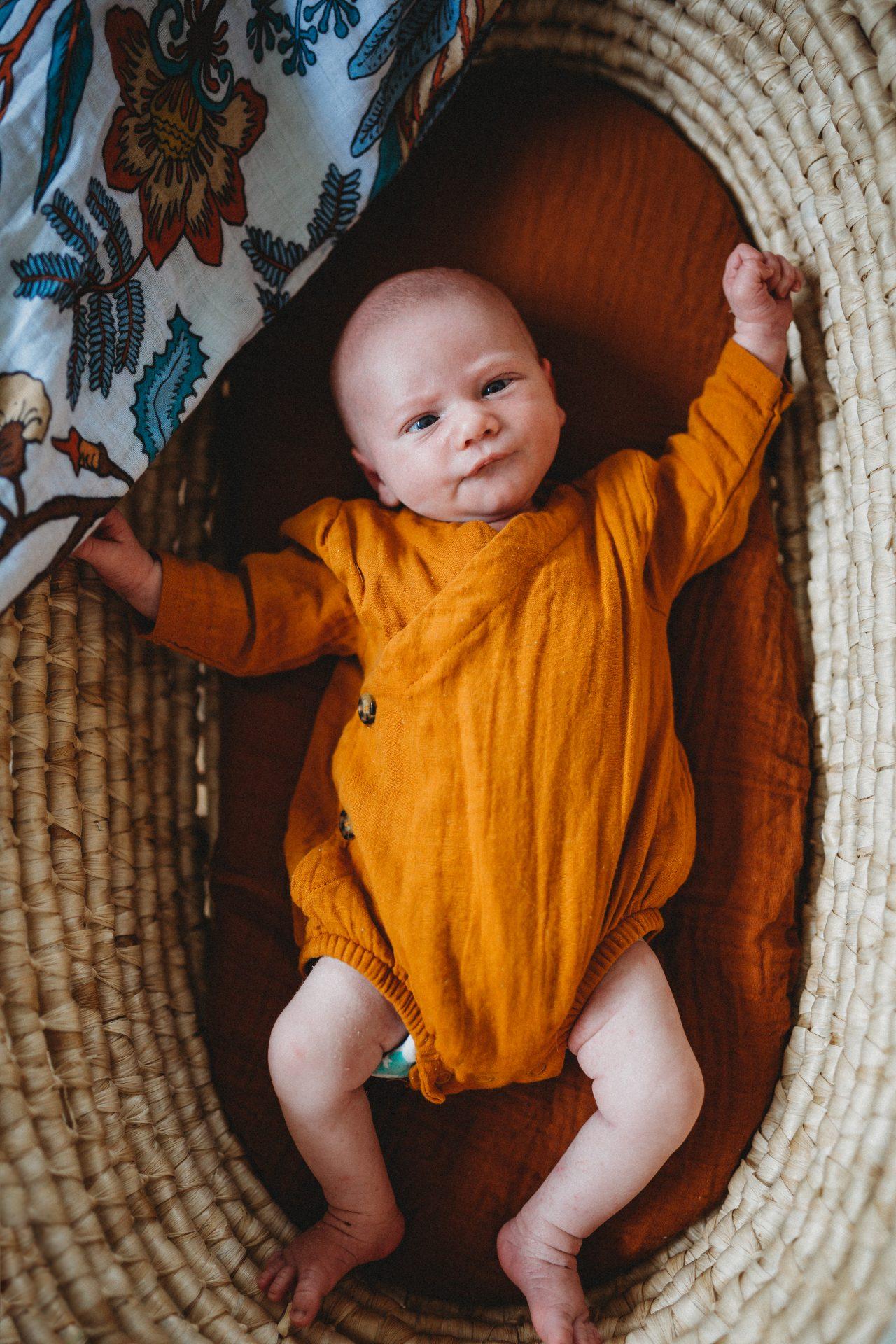 Newborn boy in boho basket, dressed in orange onesie