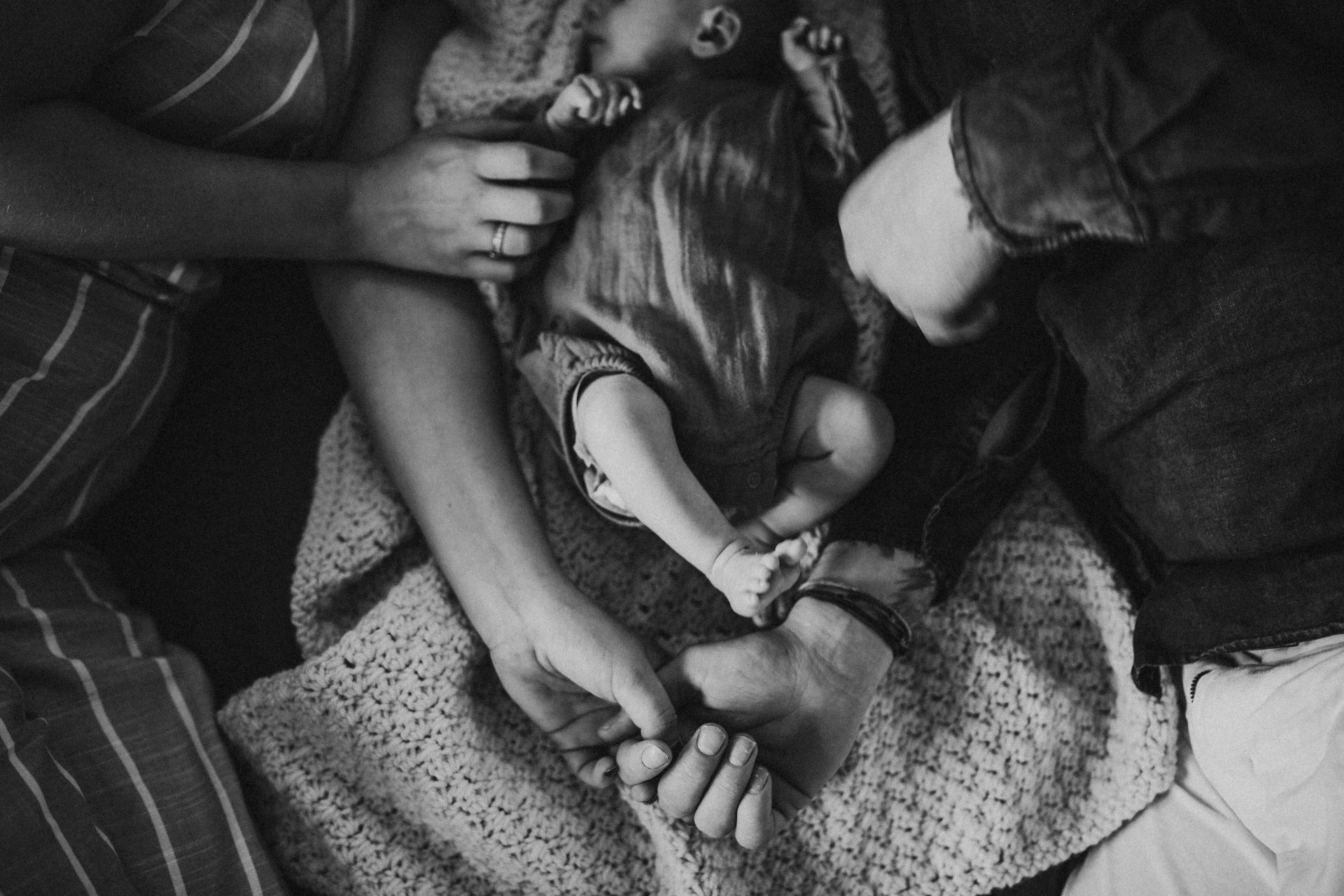 Black and white image of hand holding and hands touching baby in between parents